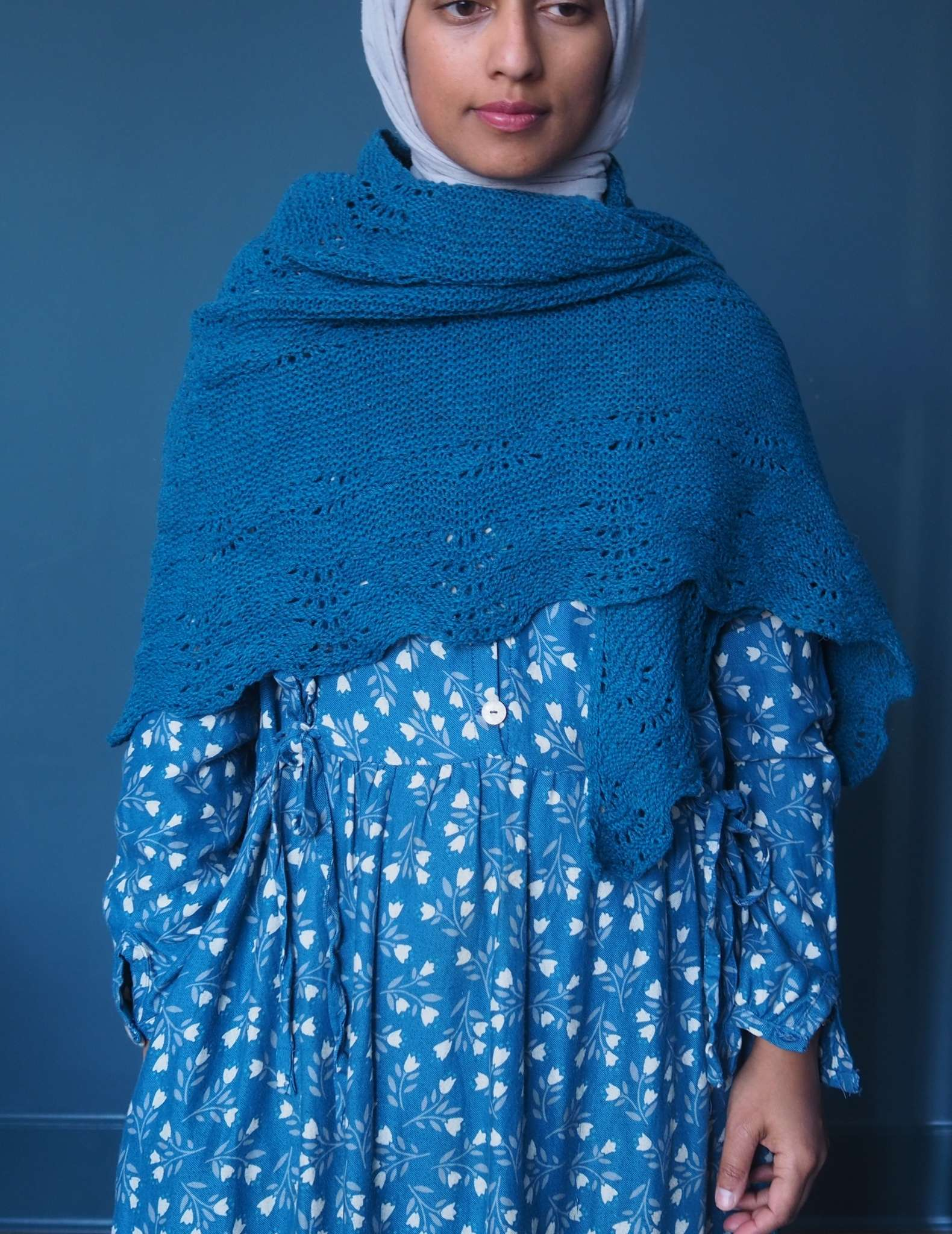 A brown woman in a hijab stands in front of a dark blue background. She is wearing a blue dress with small white floral print and a dark blue shawl which is wrapped around her chest and shoulders.