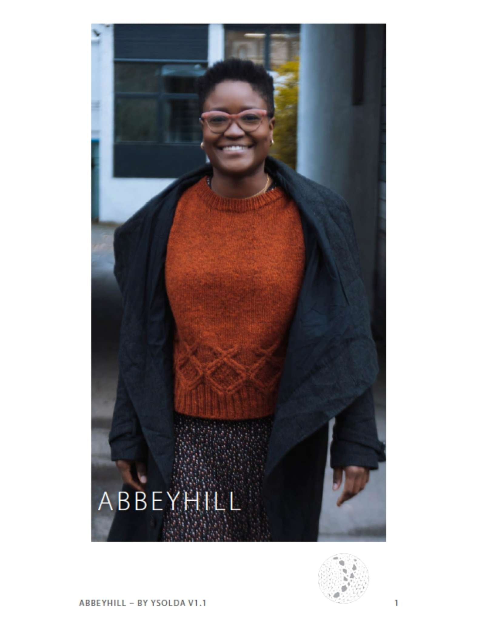 image of a black woman wearing an orange sweater and open, dark jacket. She is walking towards the camera and smiling.