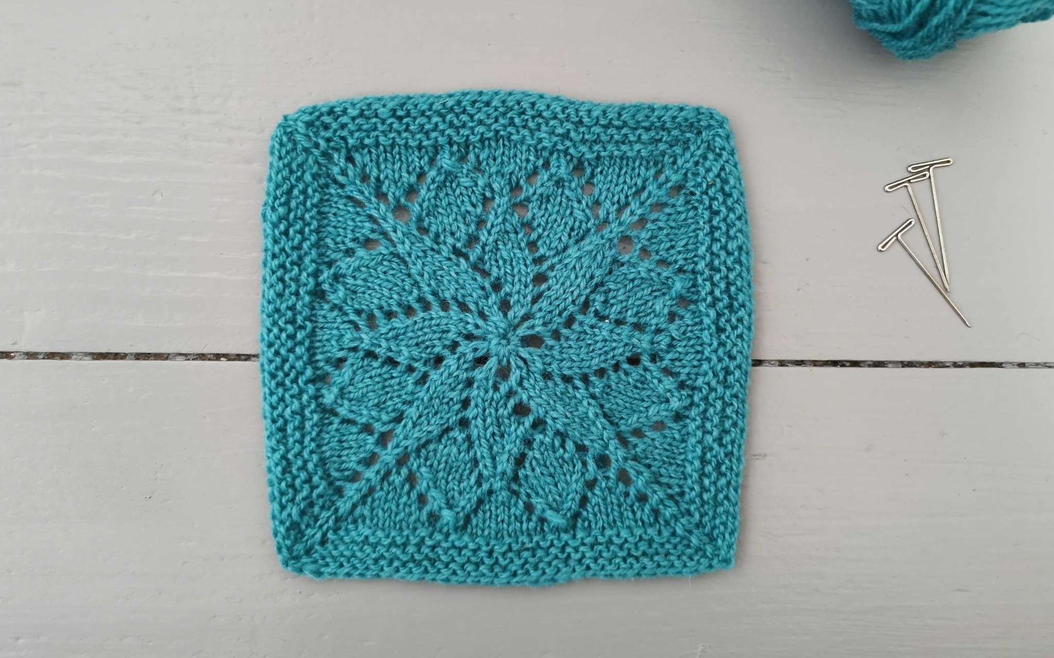 a square lace swatch of knitting, with three t-pins to the right and a glimpse of the ball of yarn used.