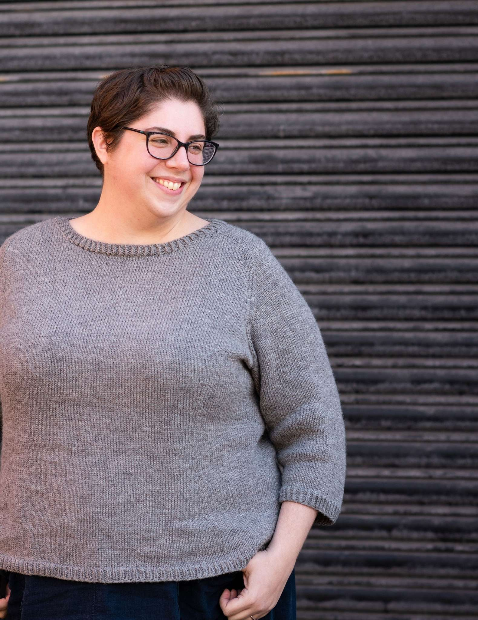 A white plus-size woman with dark hair and glasses wears a grey sweater, she is smiling and looking to the side with one hand resting on the top of a pocket