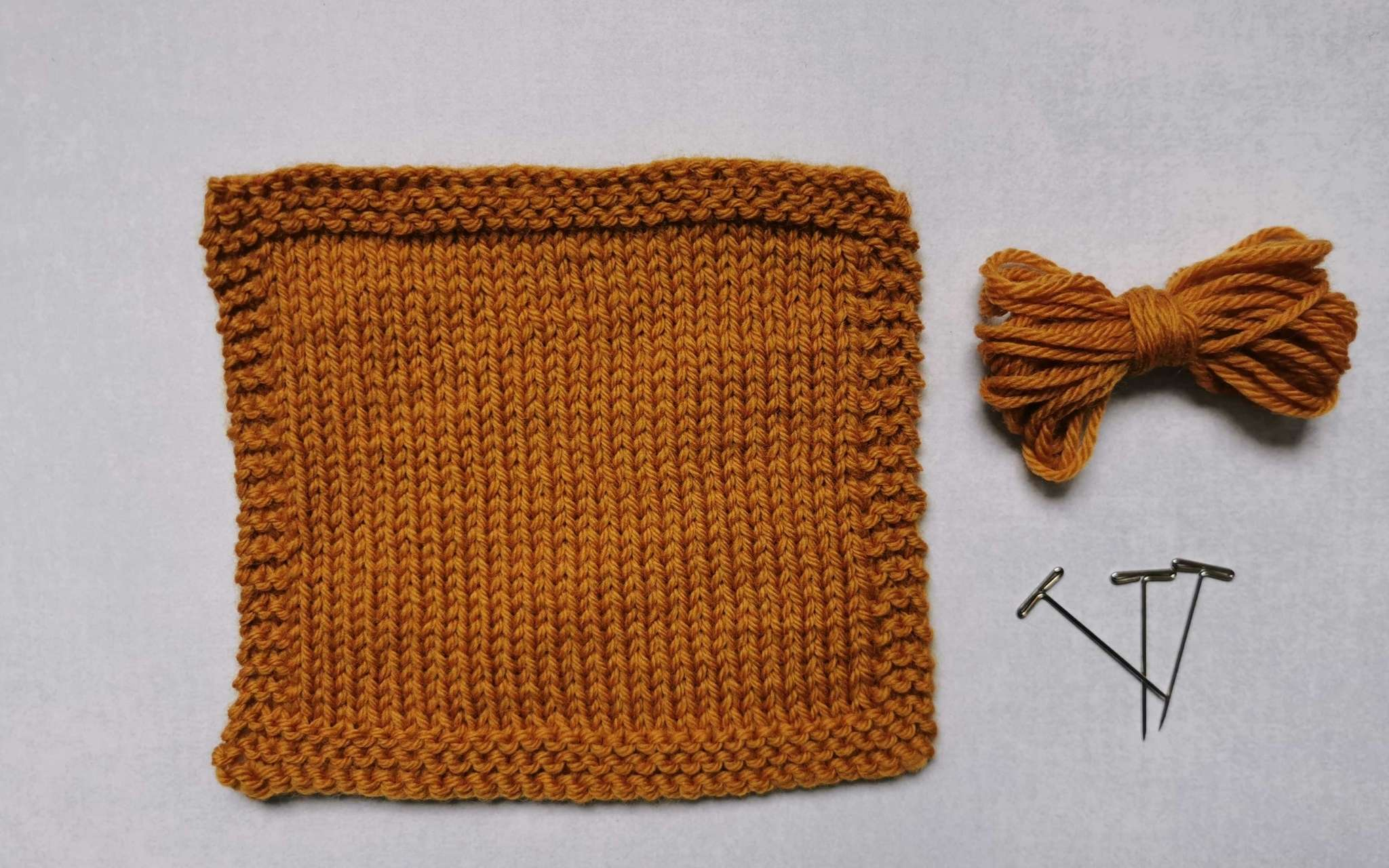 A square swatch of stocking stitch in golden yellow, with some bundled up spare yarn and t-pins laying beside it to the right.