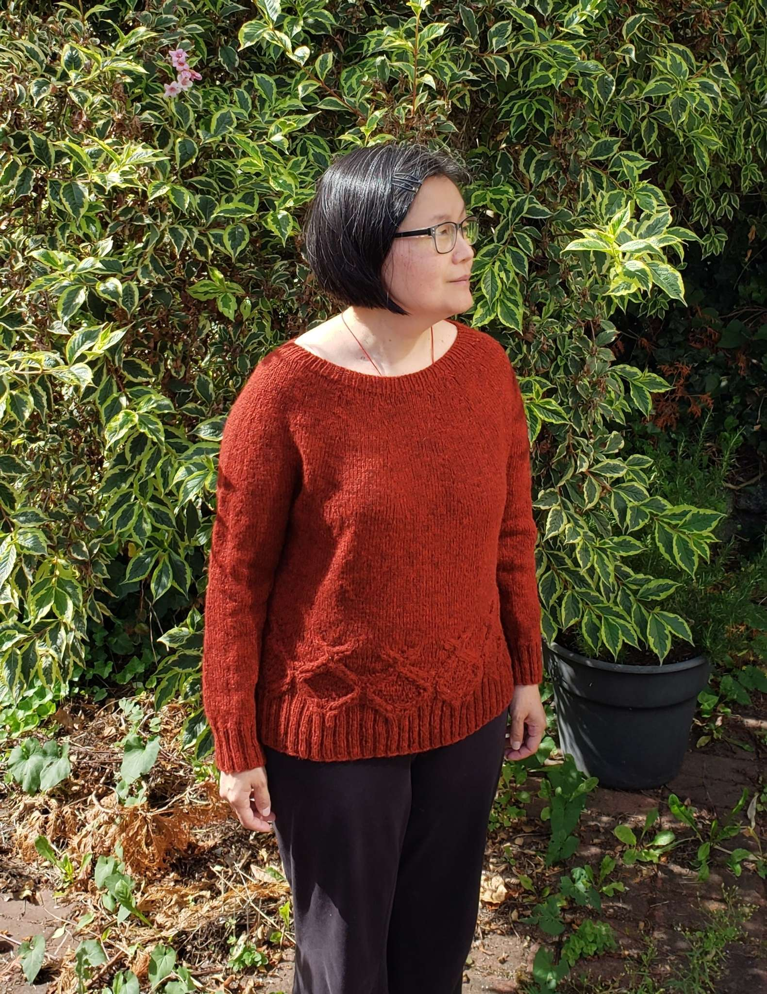 a model with dark hair wearing an orange cabled sweater stands in front of a bush, looking to the side
