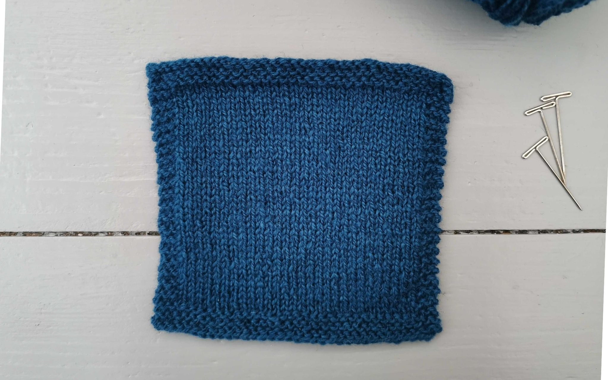 a square navy swatch of knitted fabric, with a tiny glimpse at the ball of yarn used in the corner and three t-pins at the side