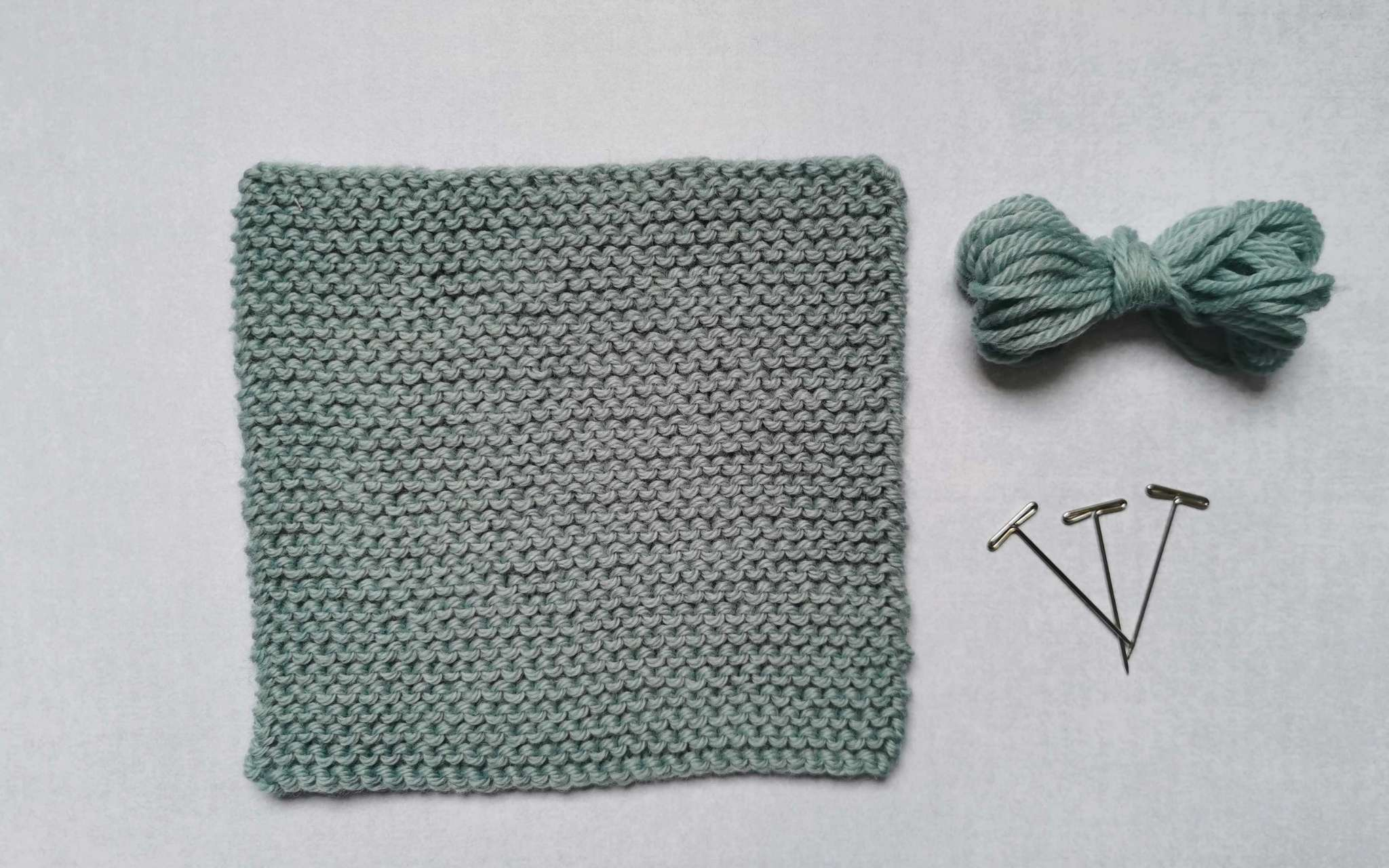 A square swatch of stocking stitch in pale blue, with some bundled up spare yarn and t-pins laying beside it to the right.