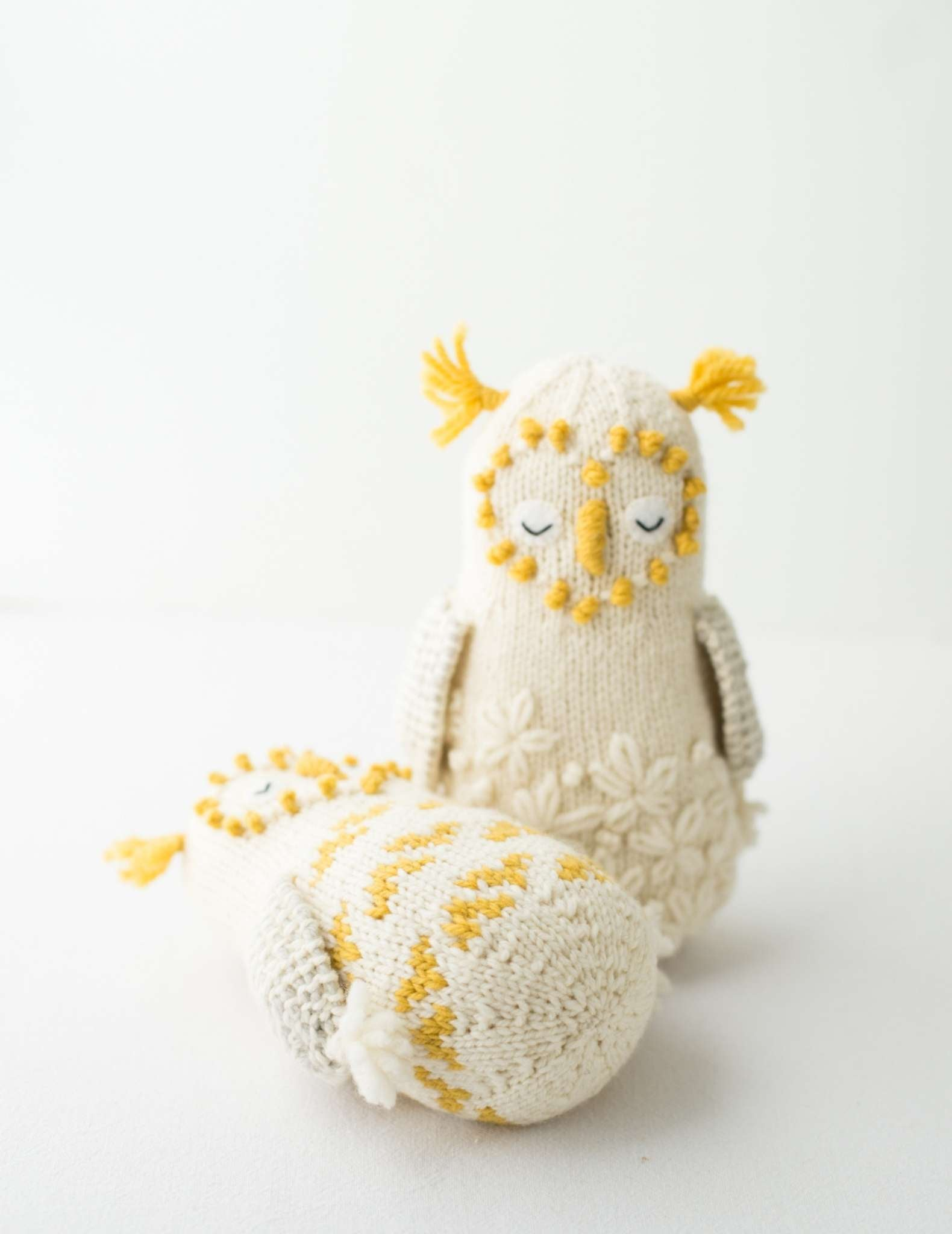 Two white knitted owls, with yellow details on the ears and face. One stands up straight at the camera, while the other lays down on its back beside the other.