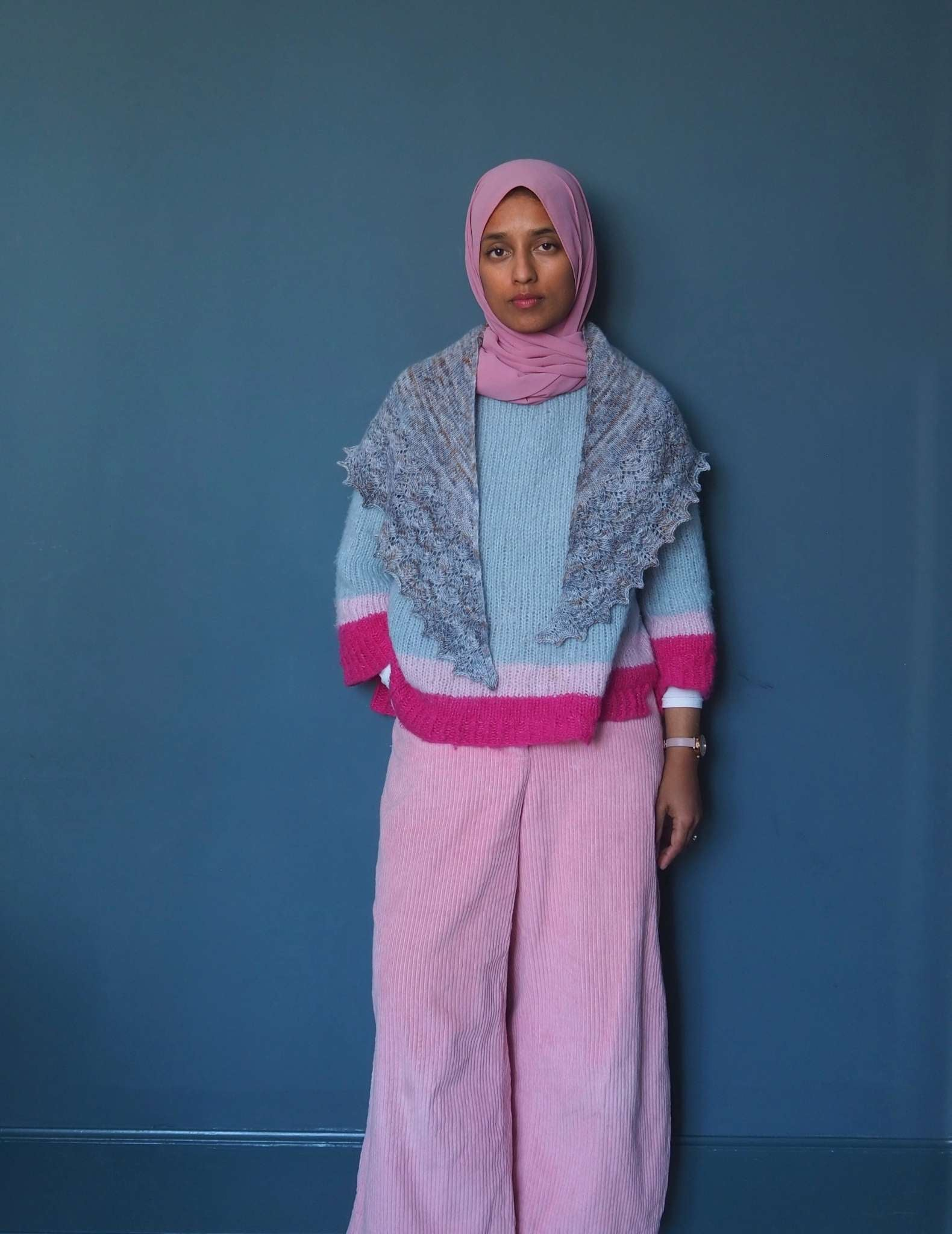 A brown woman in a pink hijab stands in front of a blue background looking straight into the camera. She is wearing a pale pastel jumper in blues and pink, pale pink trousers and a grey blue shawl around her neck with the two points hanging down in front.