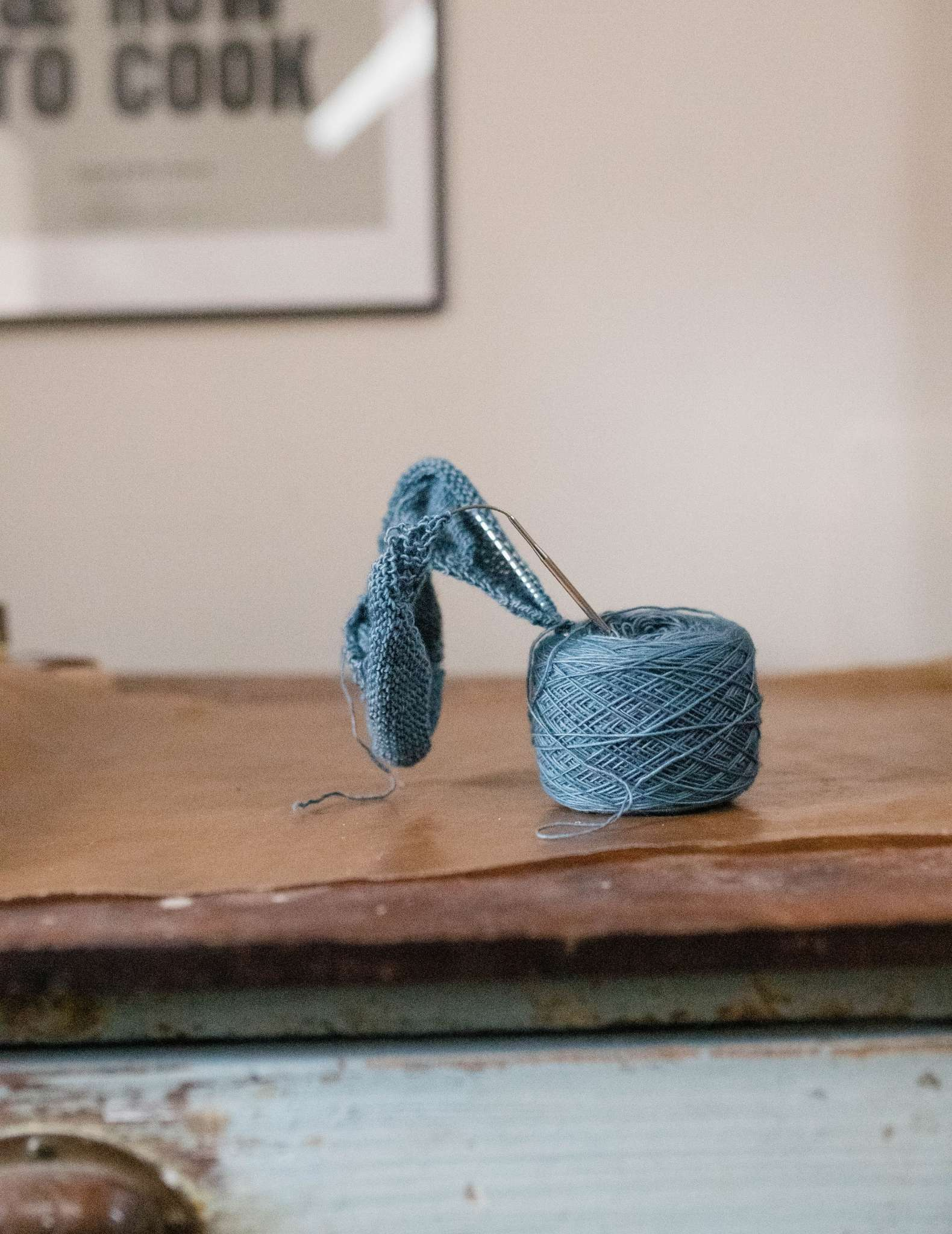 A ball of blue yarn with a project on the needles sticking out of the top of it, sitting on a wooden surface in front of a wall with an art print.