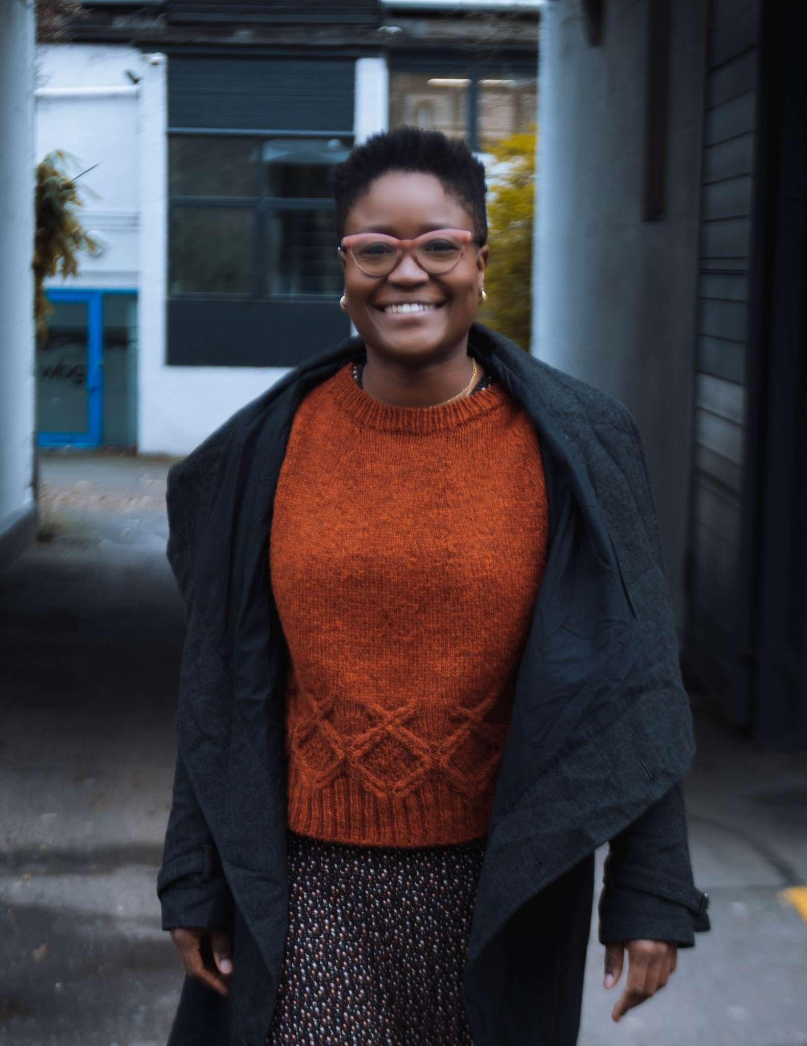 A black woman with short hair walks towards the camera wearing an orange cabled sweater, patterned skirt and a long dark jacket that hangs open.