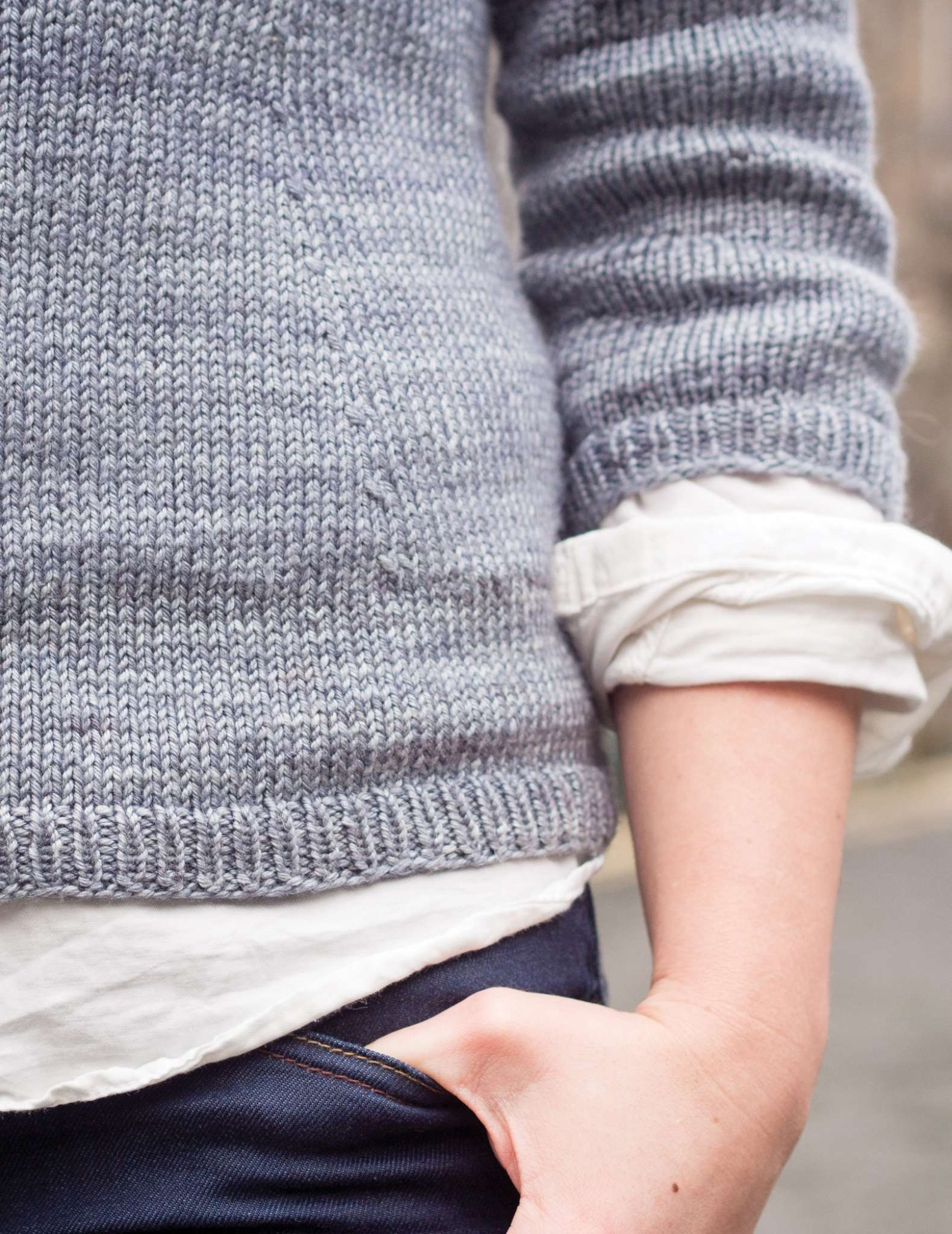 a close up of the lower side part of a grey sweater, with one arm hanging to the side with hand resting in the top of a jeans pocket. Hems of a white shirt show at the edges of the hem and cuff.