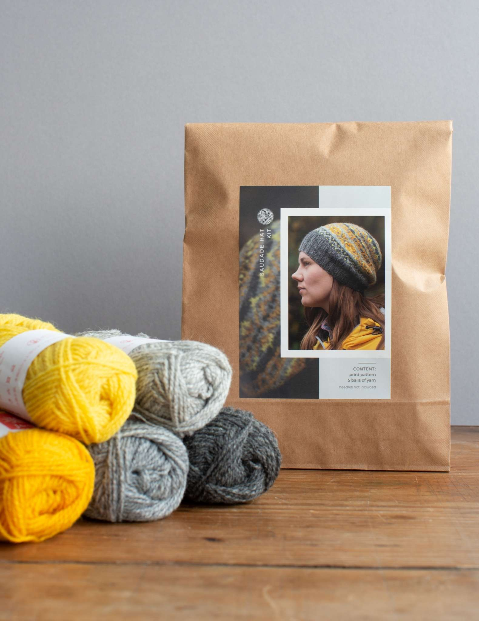 A hat knitting kit in a paper bag, sitting beside 5 balls of yarn in yellow and greys.