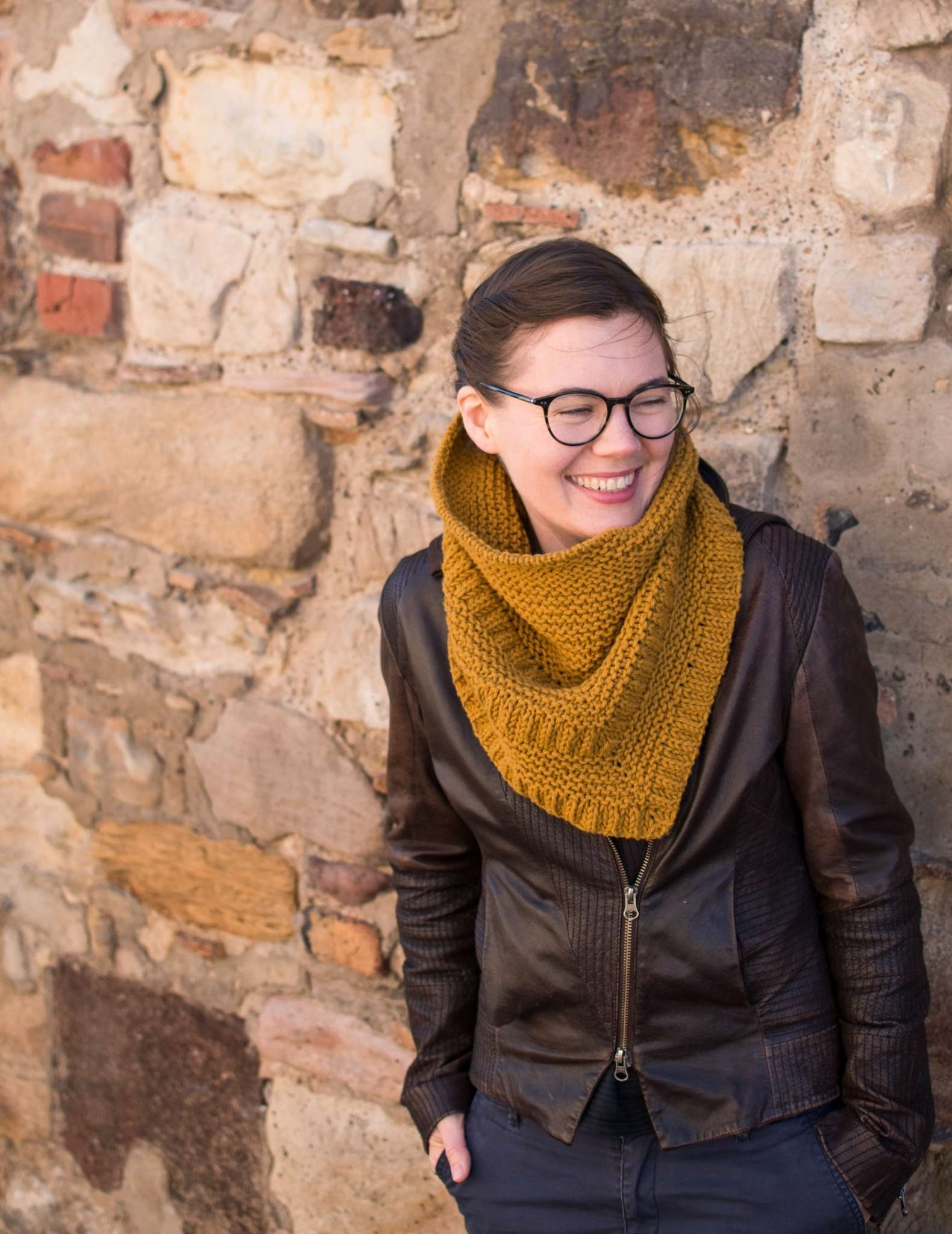 A white woman with tied back brown hair and glasses leans against a brick wall. She is laughing at something off camera, and wears a chunky golden cowl and leather jacket.
