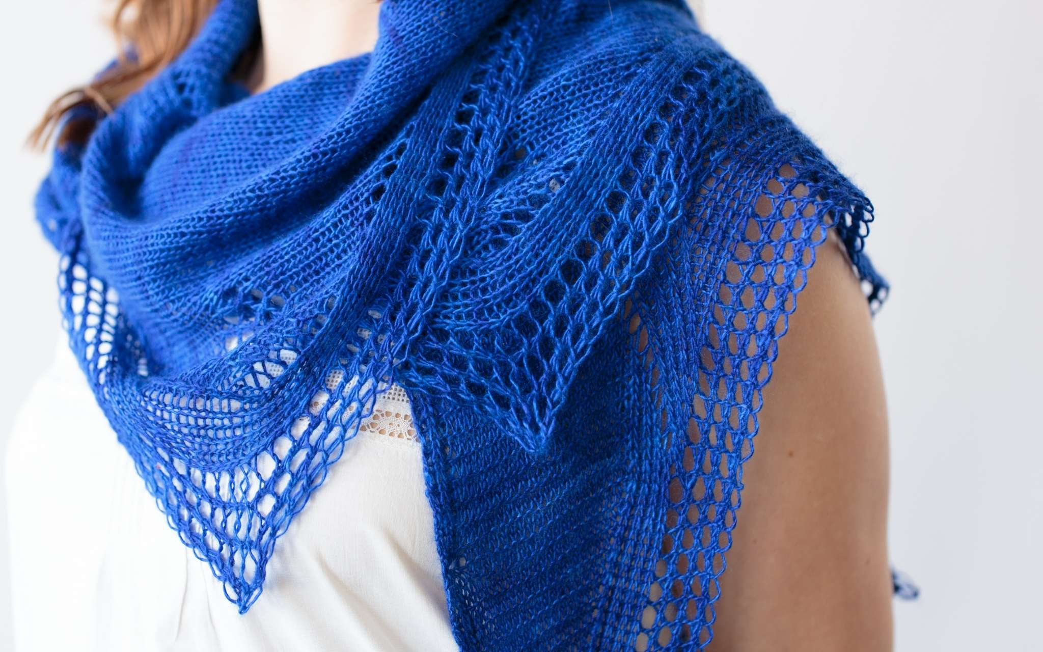 A close up of a vivid blue shawl, wrapped around the shoulders of a white model. The shawls is delicate and lacey with strong points.