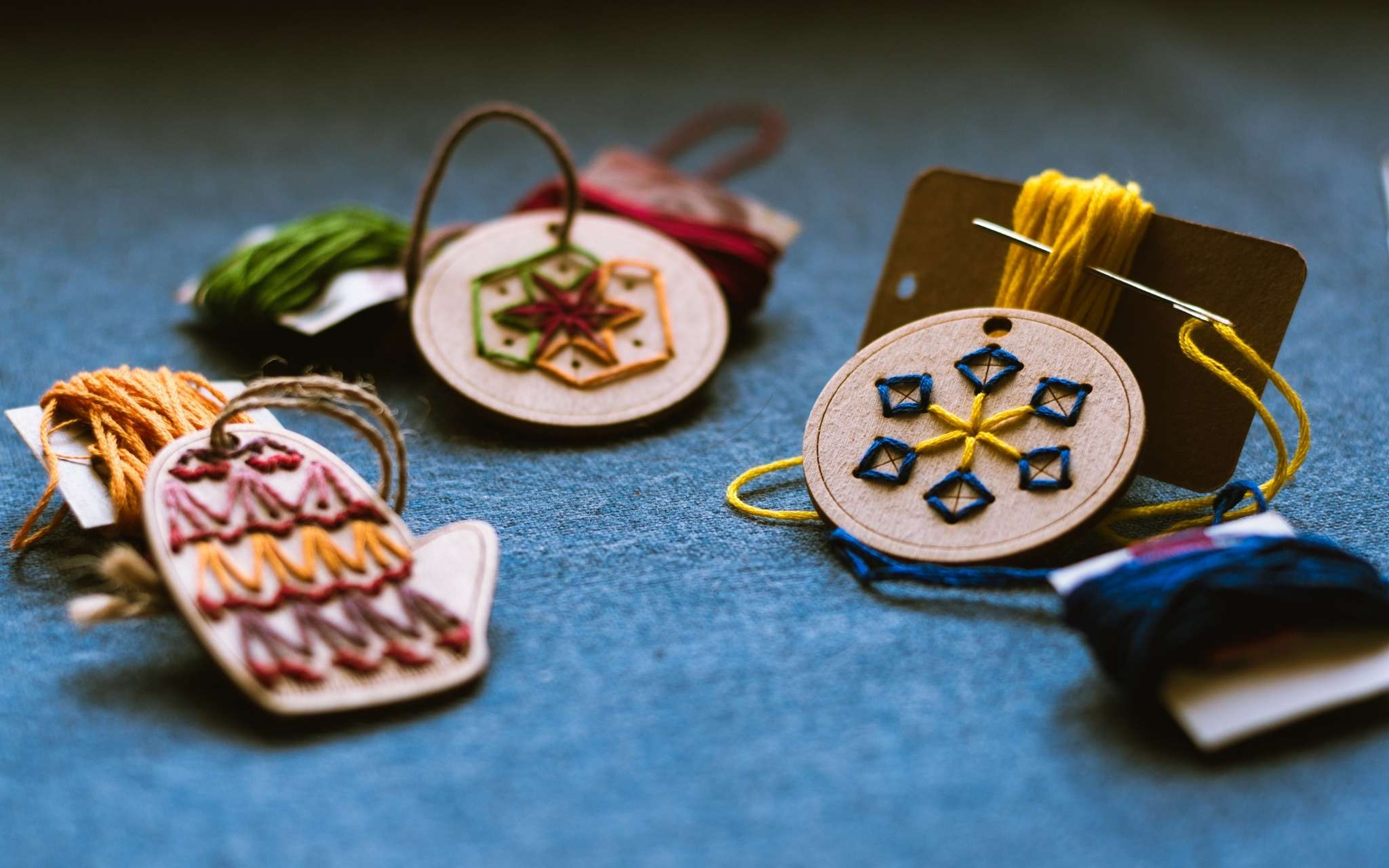 Wooden hanging ornaments shaped as mittens, a circle and a snowflake have been hand stitched through holes in the wood with brightly coloured threads.