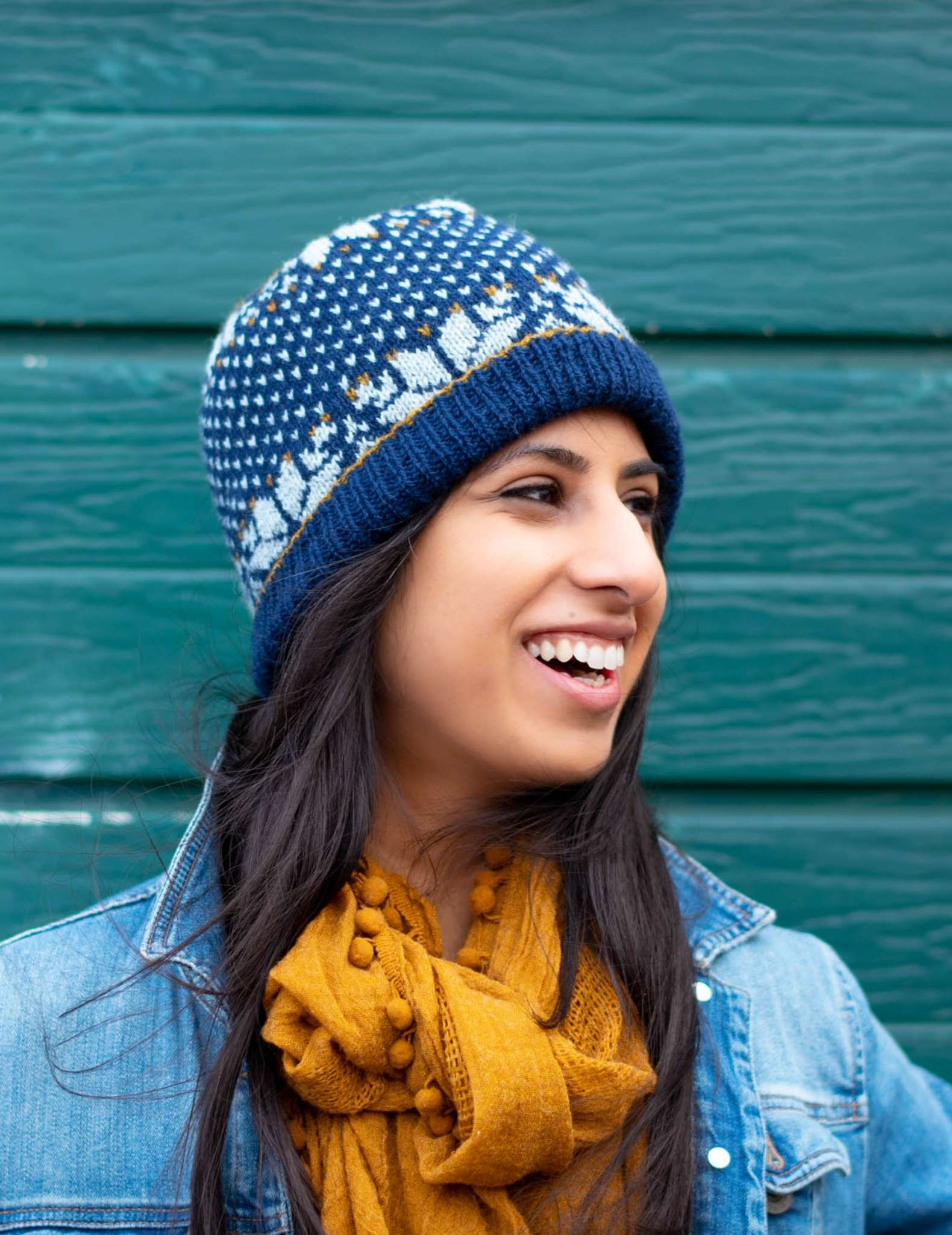 a woman with dark hair wears a dark blue and white colourwork hat, a yellow scarf and open denim jacket