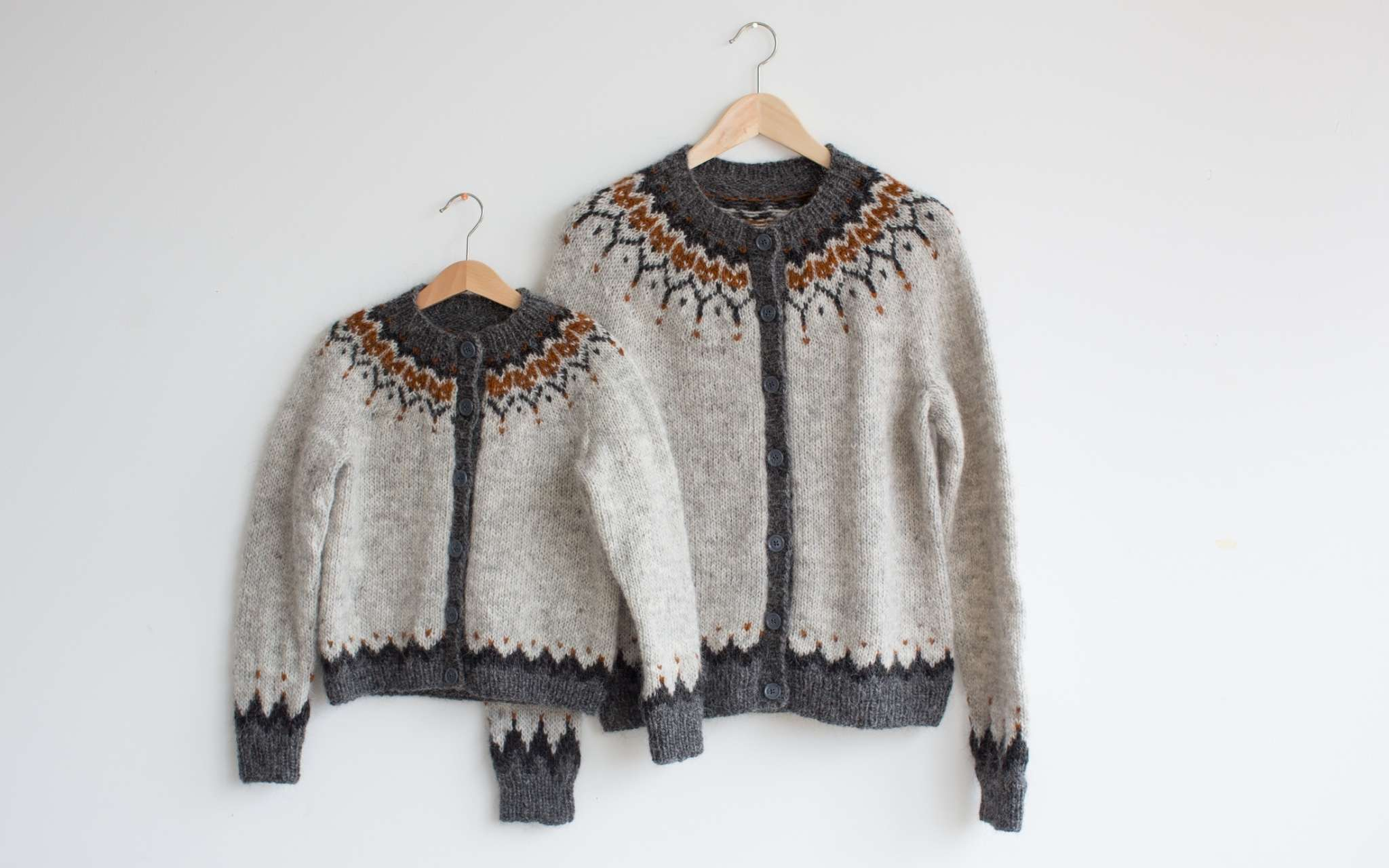 Matching adult and kid sweaters hang on wooden clothes hangers, overlapping against a wall. Both sweaters are grey, with a darker grey and orange colourwork yoke pattern.
