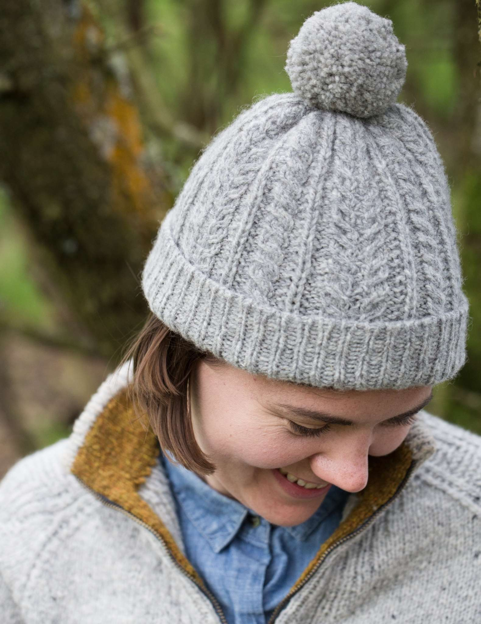 A white woman wearing a grey sweater and blue shirt looks down smiling, she wears a cabled grey hat with pom pom and a turned up ribbed brim.