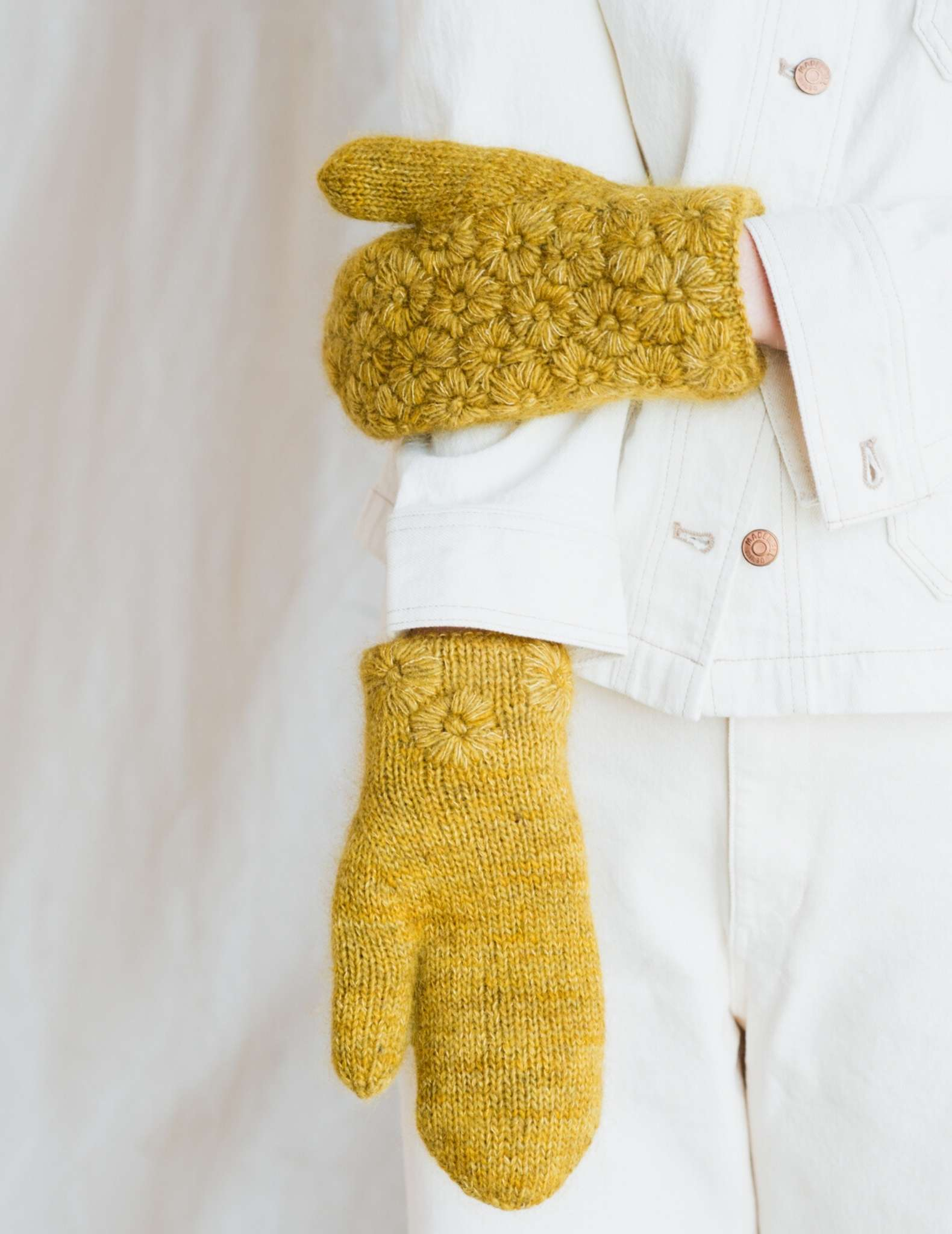 A pair of mittens are worn by a model wearing white, one arm is behind held straight down with palm side up, the other hand is resting on the straight arm, showing the detailed back of the yellow mitten