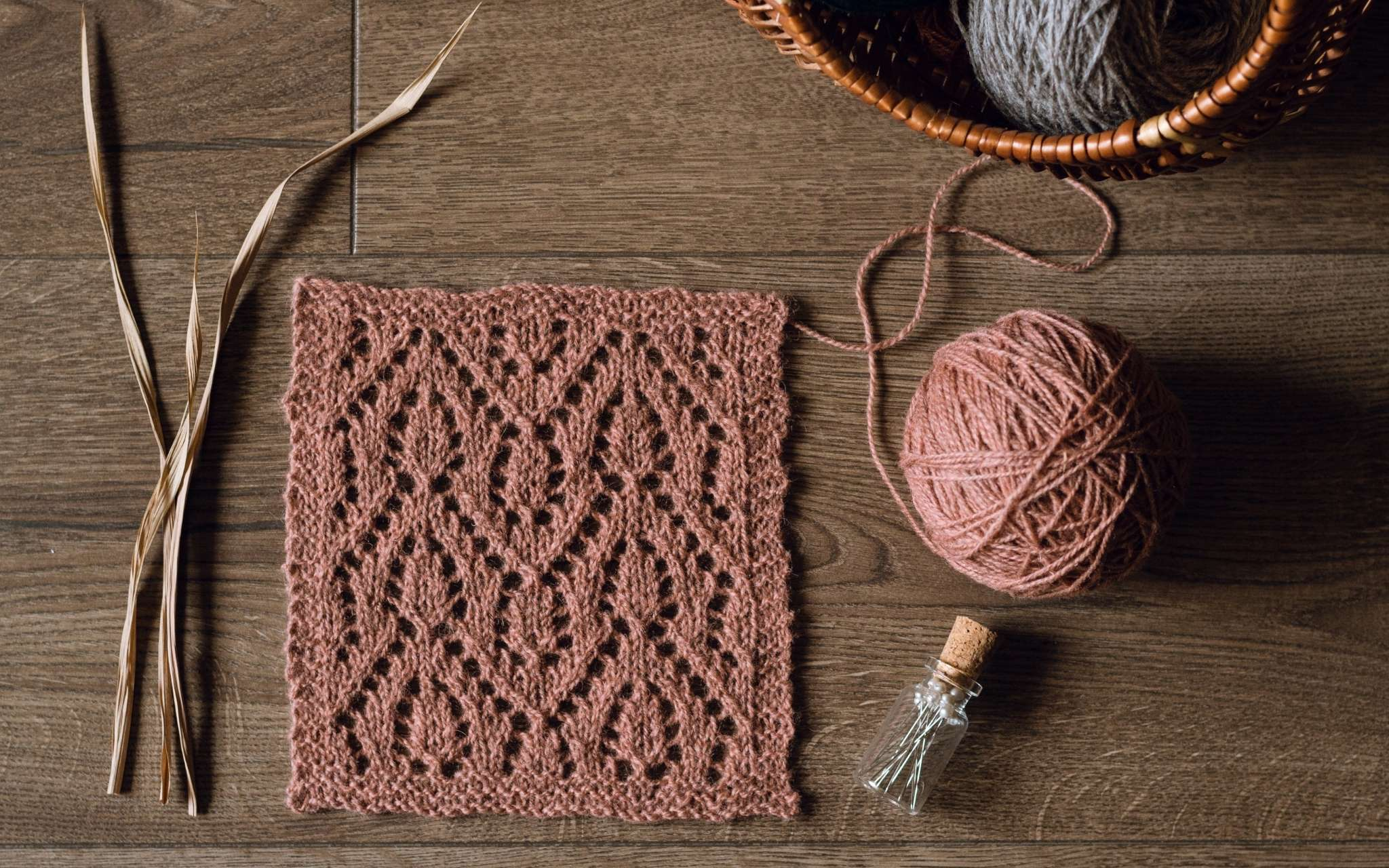 A swatch of lace in coral laid flat on a wooden surface. There are some dried stems, scissors and a bottle of pints to the side.