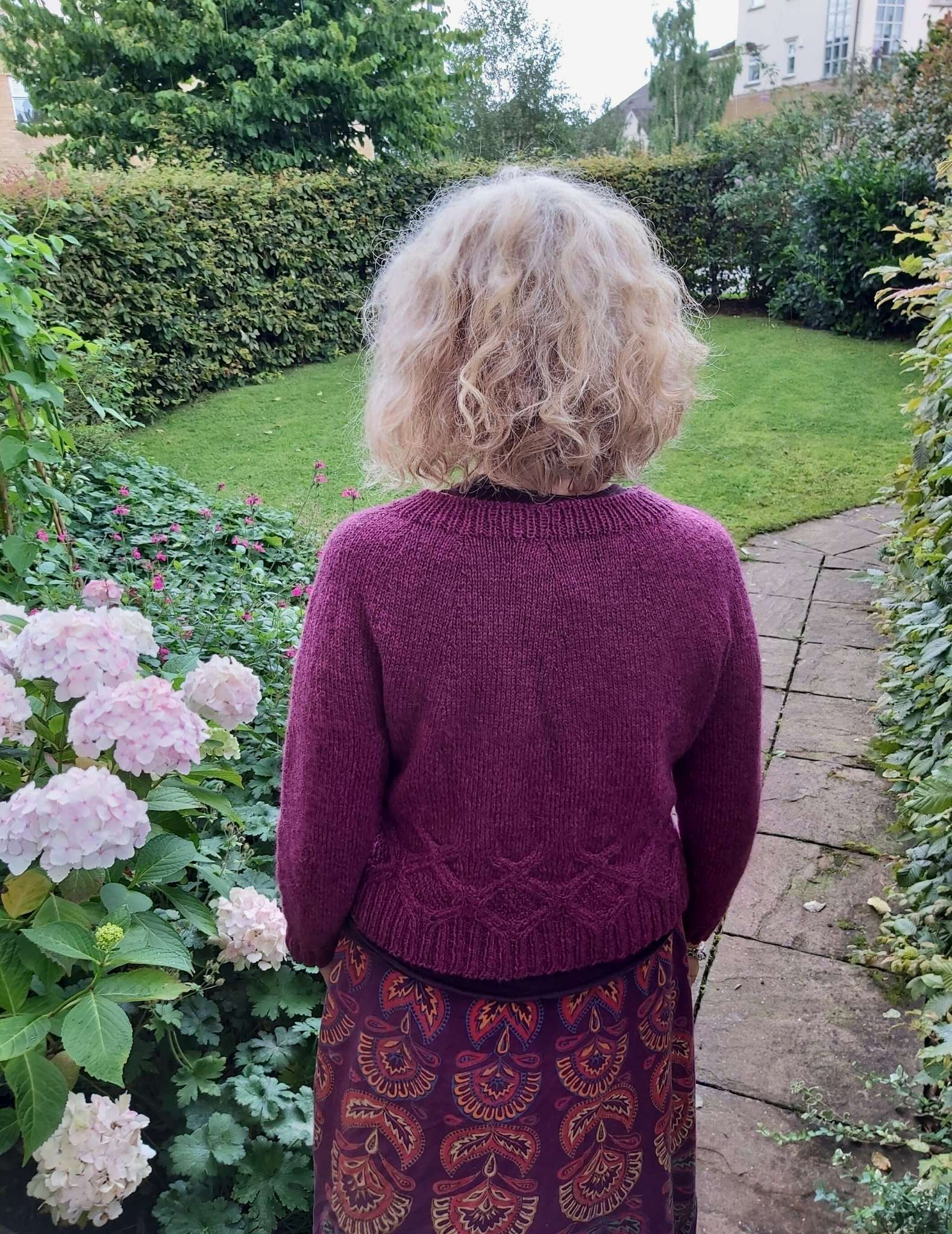 The back of a model standing outdoors wears a purple sweater