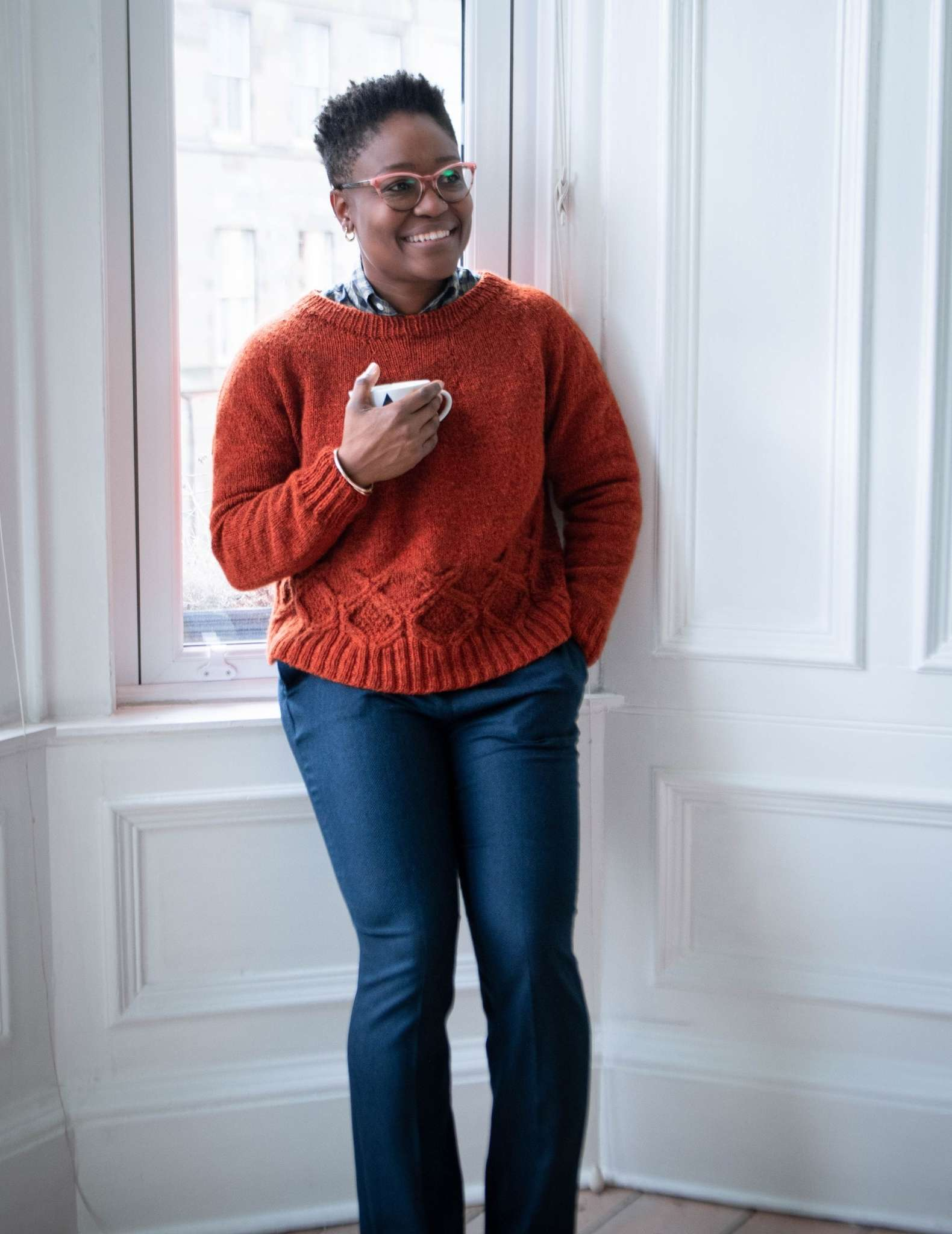 A black woman relaxes against a white indoor wall, wearing an orange cabled sweater and jeans and holding a mug in her right hand.
