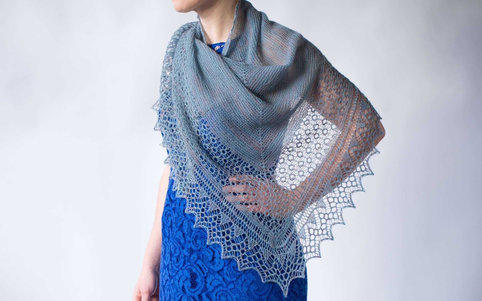 A close up of a delicate pale grey shawl, worn by a model wearing a blue dress. The model's head is not visible, but they are standing in front of a white background with their left hand resting on their hip.