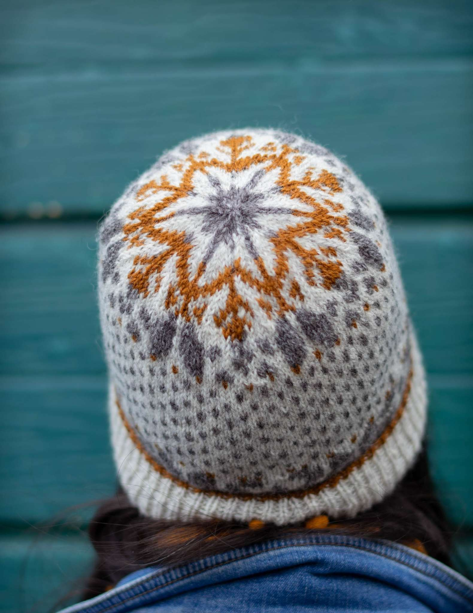 A colourwork hat with snowflake motif in cream, grey and brown. The hat is worn by a model in front of a teal wall, and only the back of the hat is visible