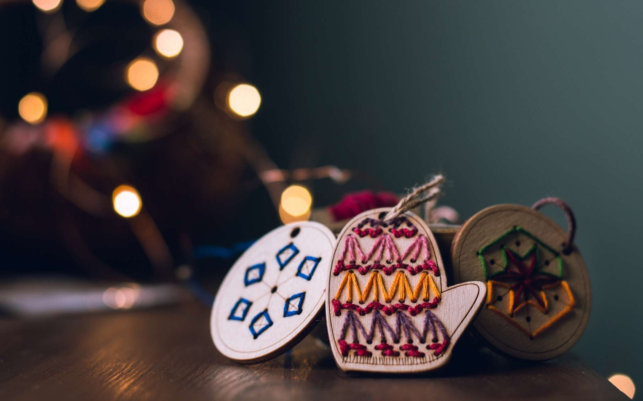 Wooden hanging ornaments that have been hand stitched in bright colours are gathered on a wooden surface, with fairy lights and a tree blurred behind.