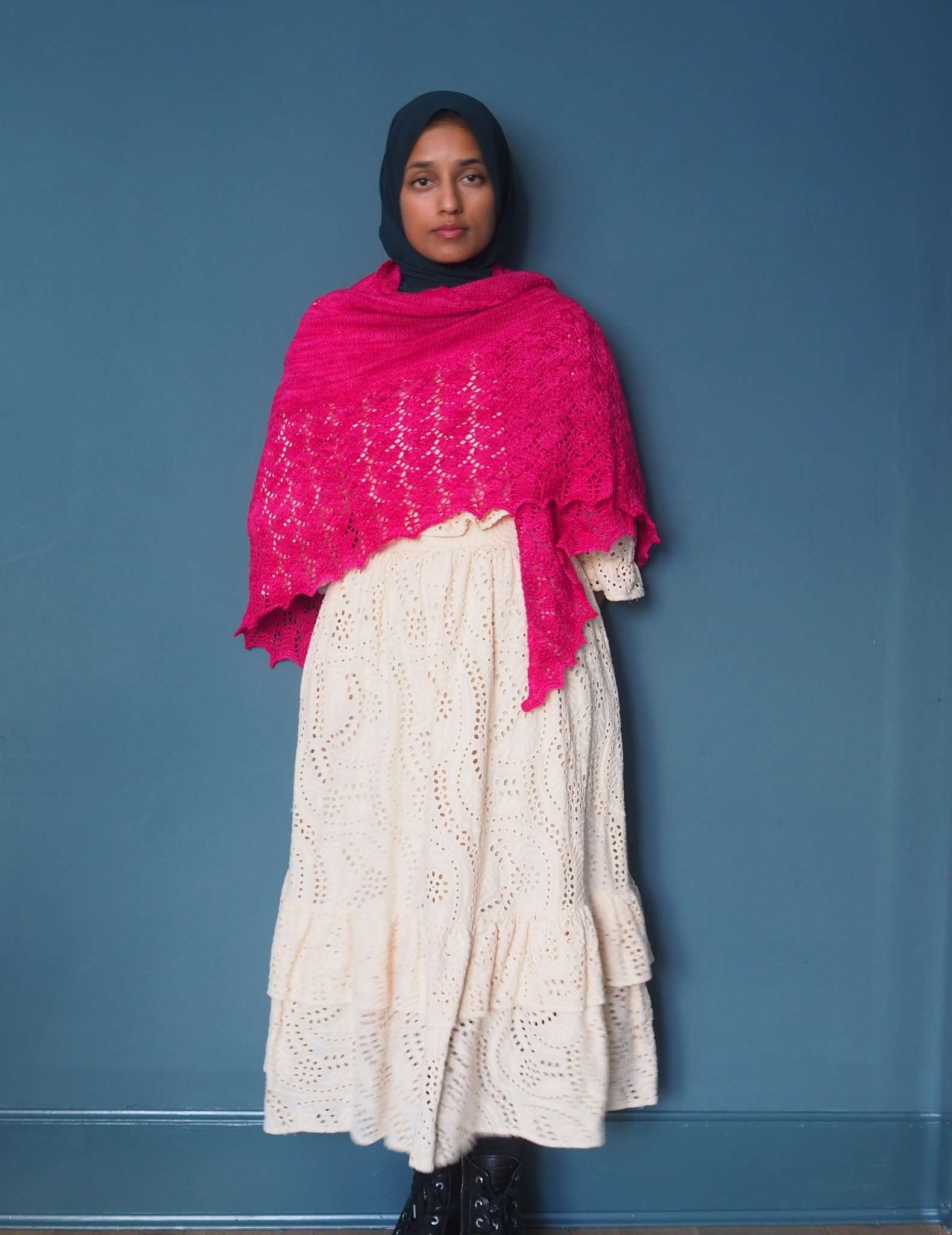 A brown woman in a hijab stands in front of a dark blue background. She is wearing a floaty cream dress with a large bright pink shawl wrapped around her shoulders and chest.