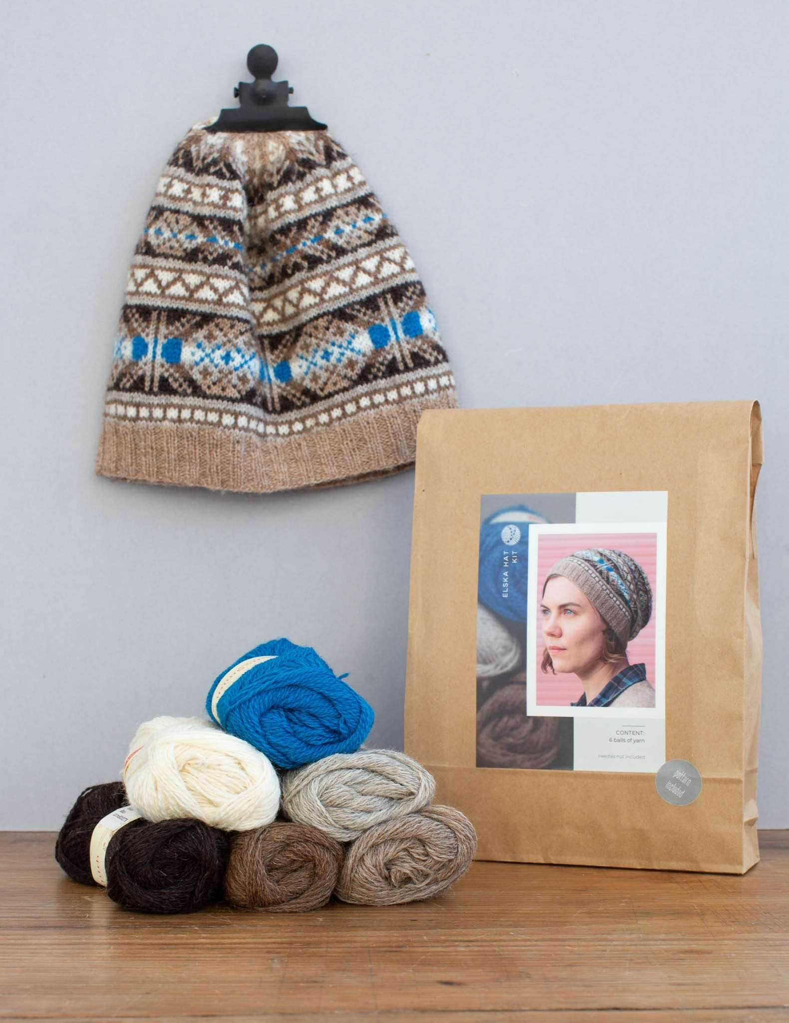 A hat knitting kit in a paper bag, with the hat hanging from the wall behind by a clip and 6 balls of yarn piled in front in blues and neutral colours.