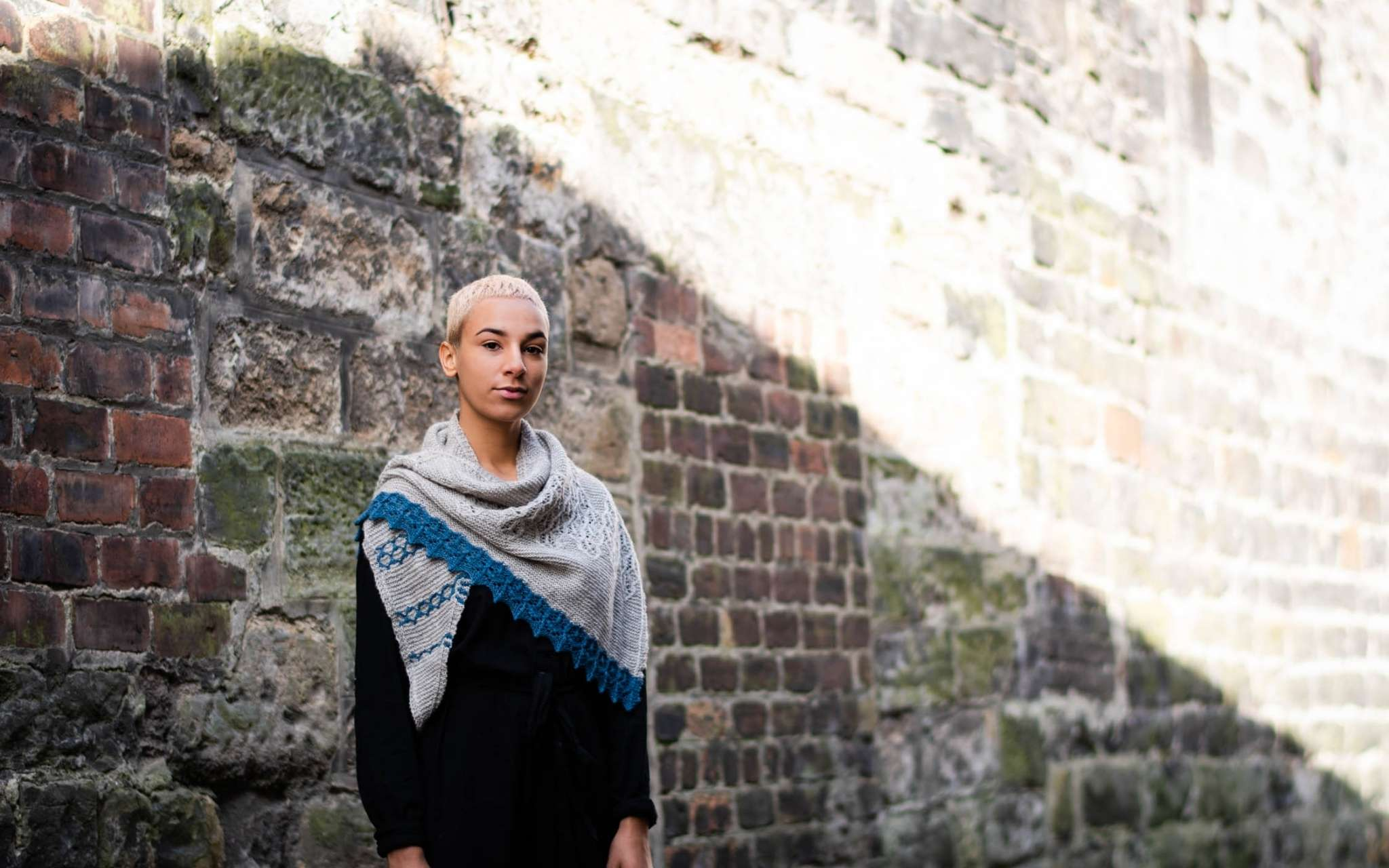 A model with short pale hair stands against a brick wall in the bright sunshine. They are wearing dark clothes, and a pale grey shawl with blue contrast edging is around their neck.