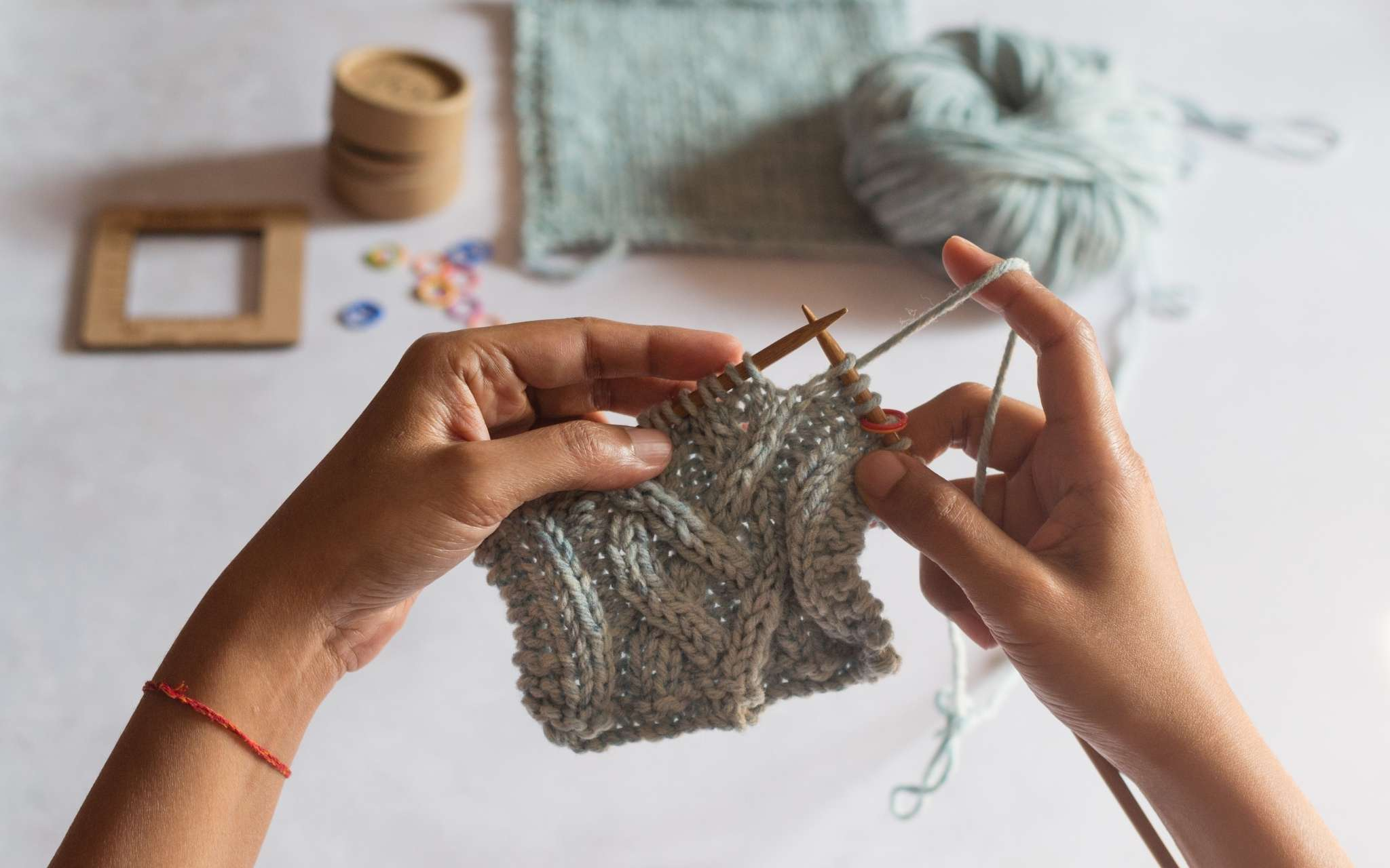 A woman of colour knits a pale blue cabled swatch on wooden needles. A completed swatch and measuring tools are on a flat surface at the top of the image.