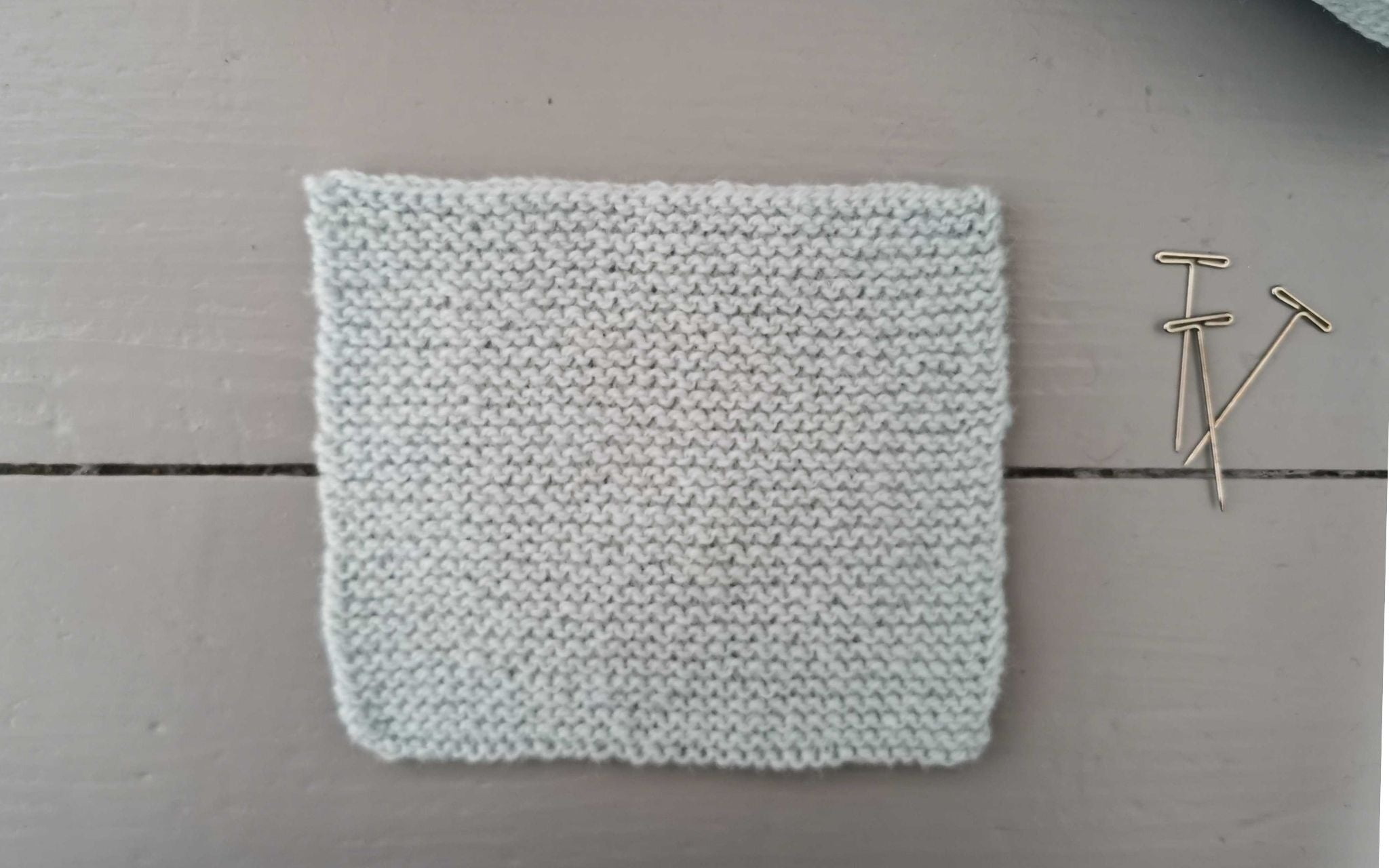 a square swatch of garter stitch in a pale blue yarn, with three t-pins at the side