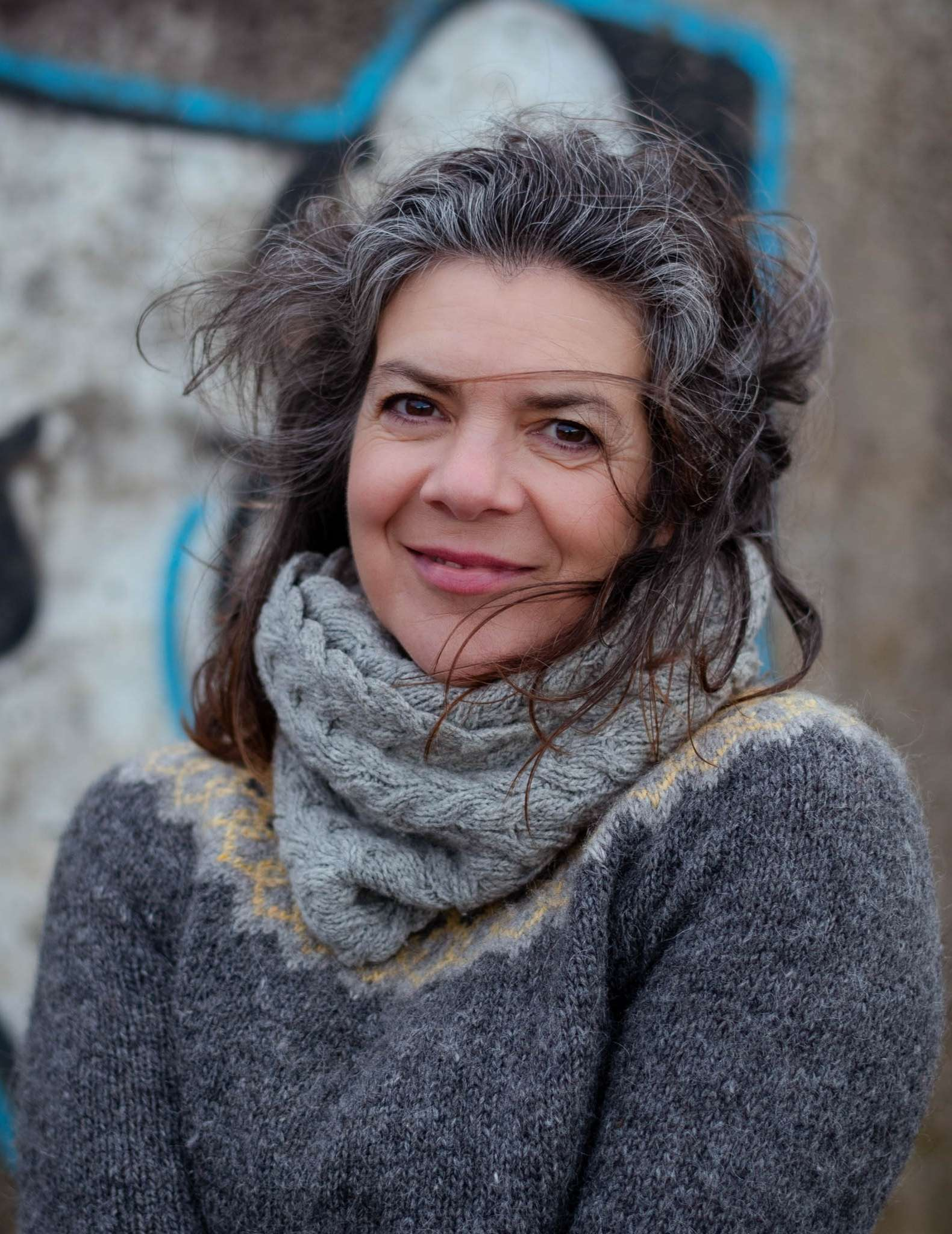 A white woman with dark hair flecked with grey wears a grey cabled cowl and grey and yellow colourwork yoke sweater.