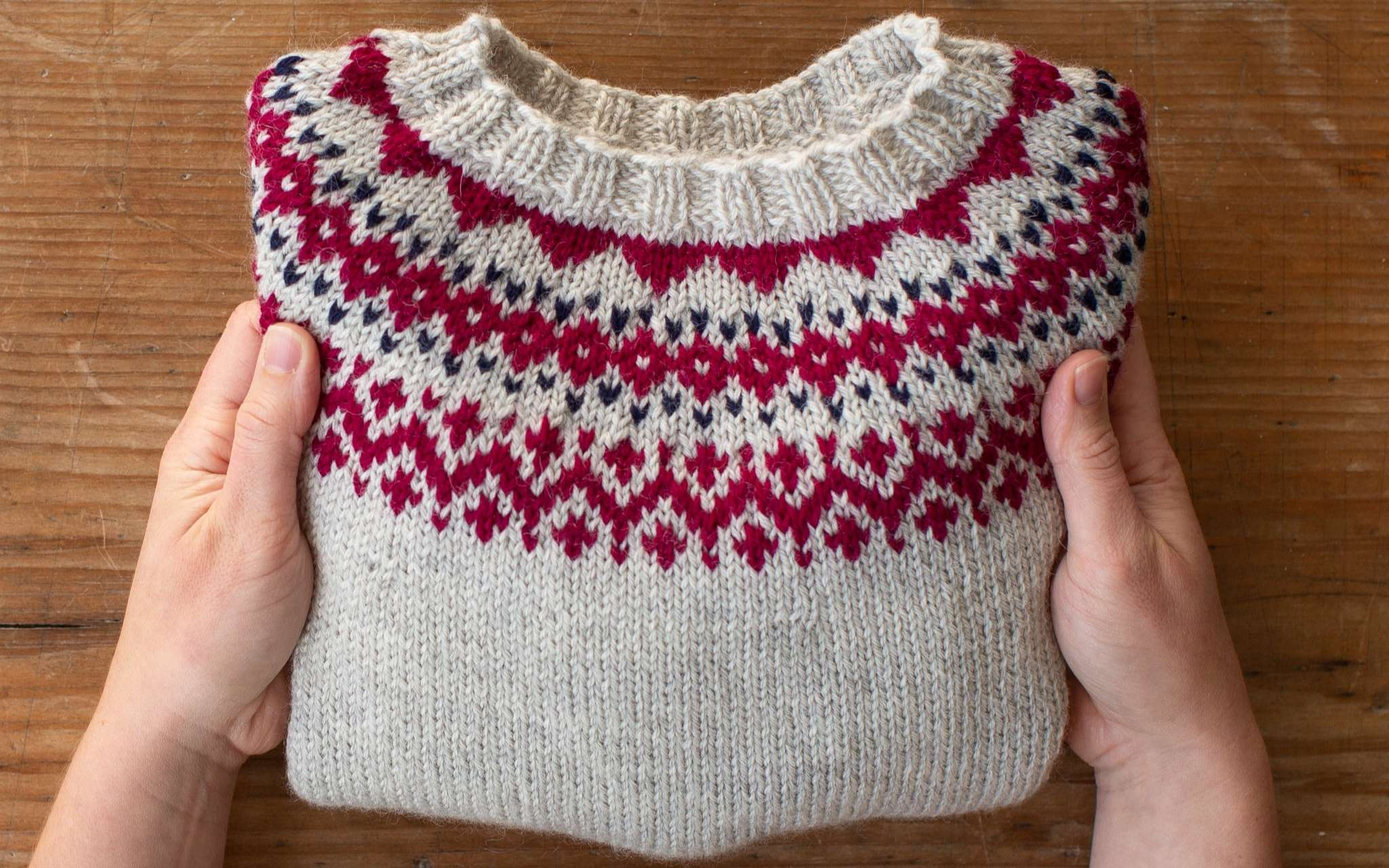 Two hands hold a folded sweater over a wooden surface. The sweater is pale grey with a pink and navy colourwork pattern around the yoke.