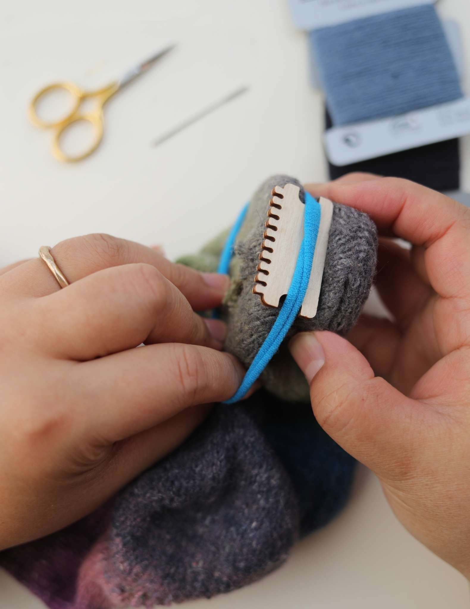 Hands are stretching a blue piece of elastic around a heddle and darning loom positioned inside the sock, securing them both together.