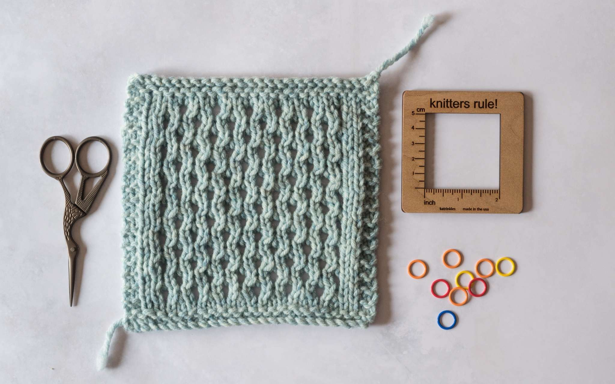 A pale blue cabled swatch lies on a flat surface. A small pair of scissors lie next to it on the left, and to the right is a square wooden swatch measuring tool and brightly coloured stitch markers.