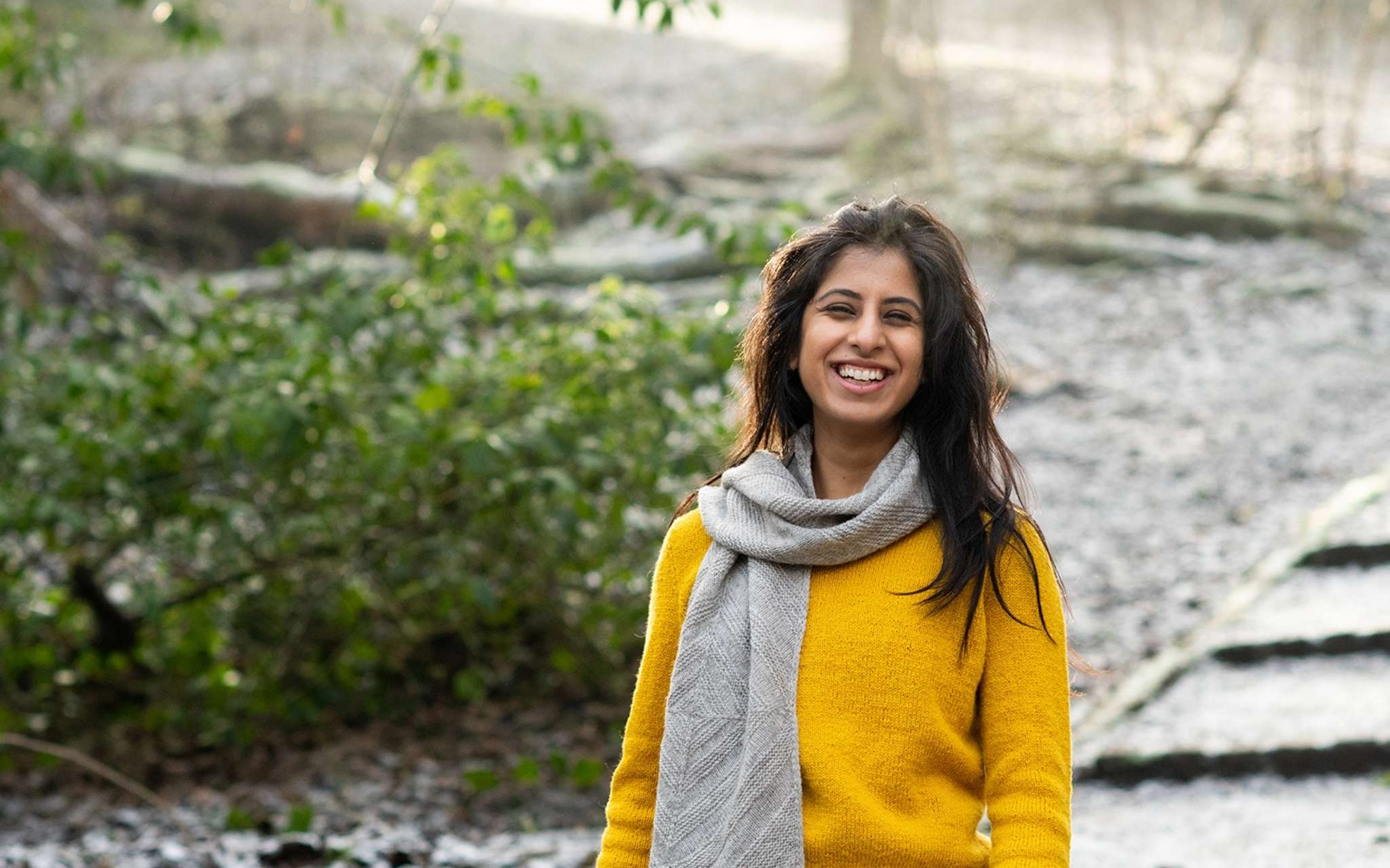 A woman of colour stands outdoors at the end of a stone path, with foliage to the left side. She has long dark hair and is wearing a yellow sweater and grey scarf which is wrapped around her neck and then hanging down to the front. She is smiling.