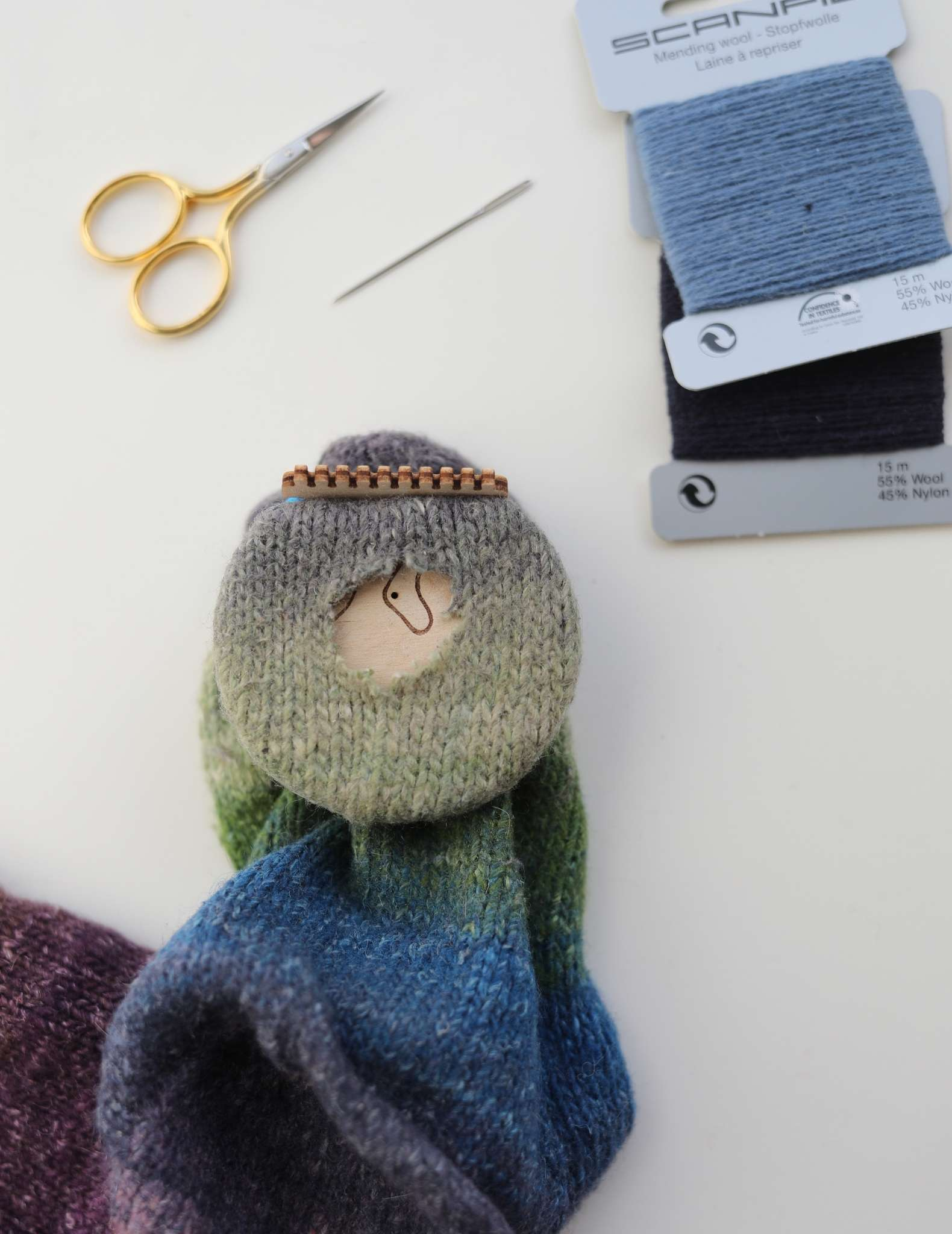 The sock with hole is shown from above, with the darning loom in position inside the sock, the heddle on the outside near the toe and both are being held in position by elastic.