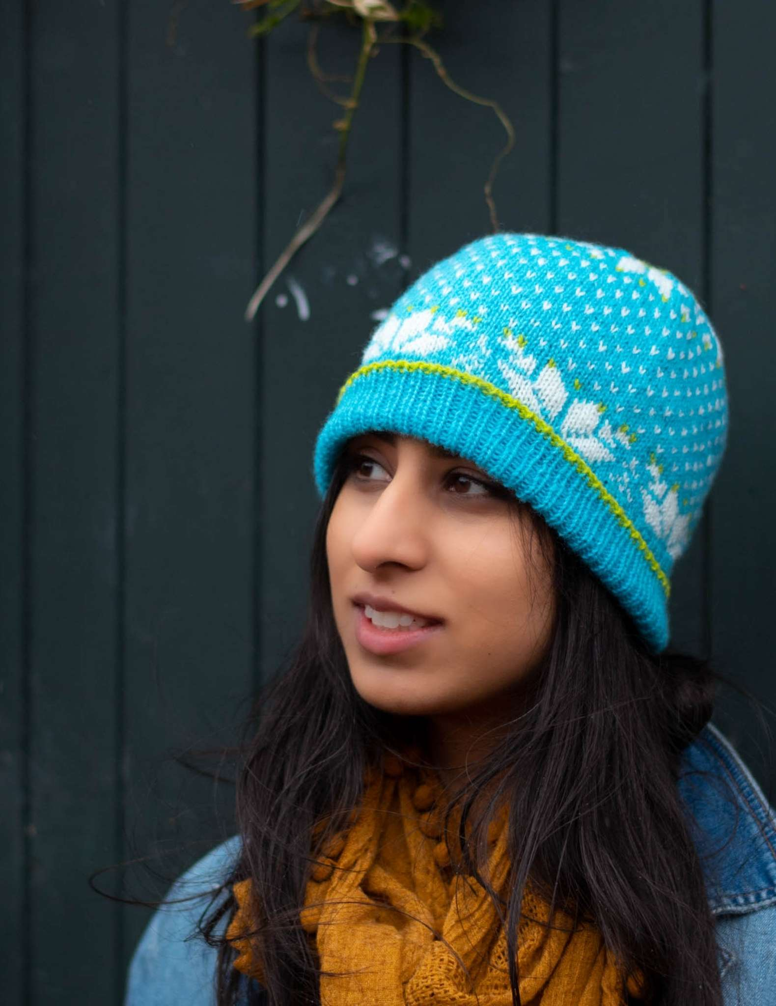a model with dark hair wears a bright blue colourwork hat with snowflake detail. They are wearing a yellow scarf and looking slightly to the side.