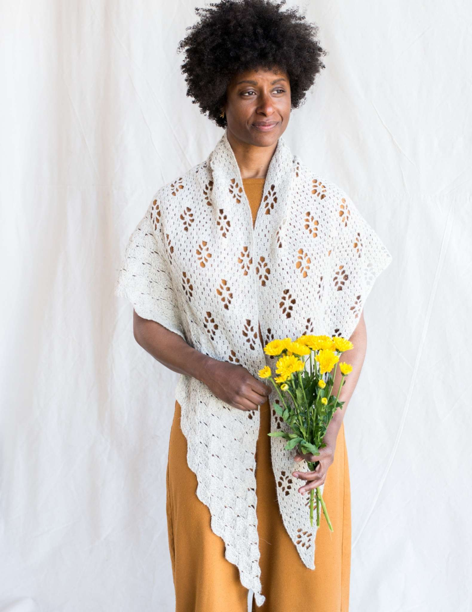 A large crocheted white shawl with lace details is worn by a black woman holding a bunch of yellow flowers. The model faces the camera with the corners of the shawl draped over each shoulder.
