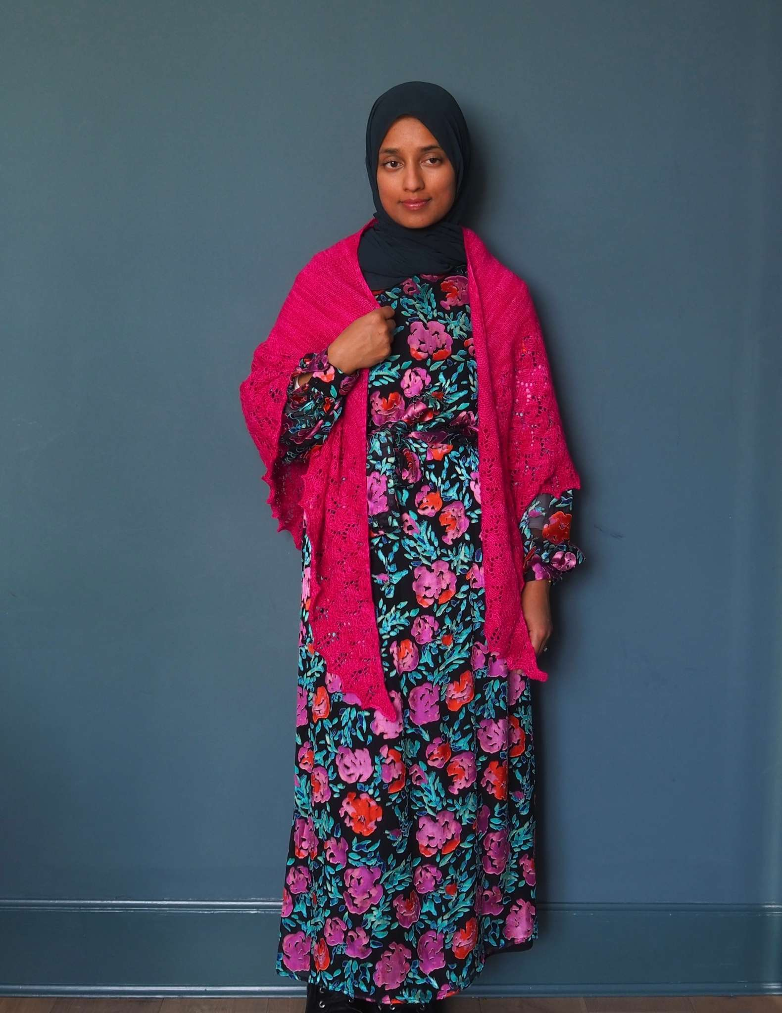 A brown woman in a hijab stands in front of a dark blue background. She is wearing a vivid floral print dress in black, pinks, orange and greens. She has a large bright pink shawl around her neck with the pointed ends hanging down at the front, and her right hand is raised and holding the straight edge of the shawl along her chest.