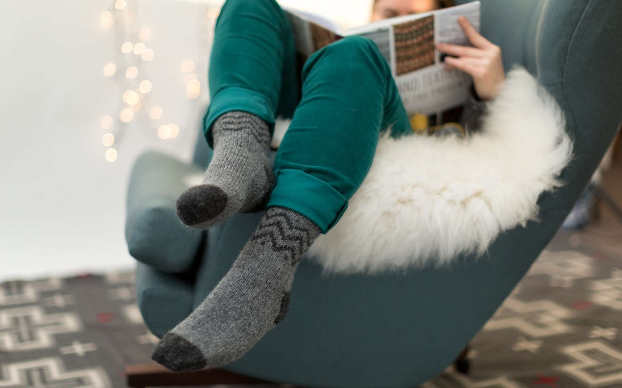 A model wears grey colourwork socks and teal trousers, while snuggled on an armchair holding a book. There are twinkling lights in the background and they sit on a fluffy white blanket.
