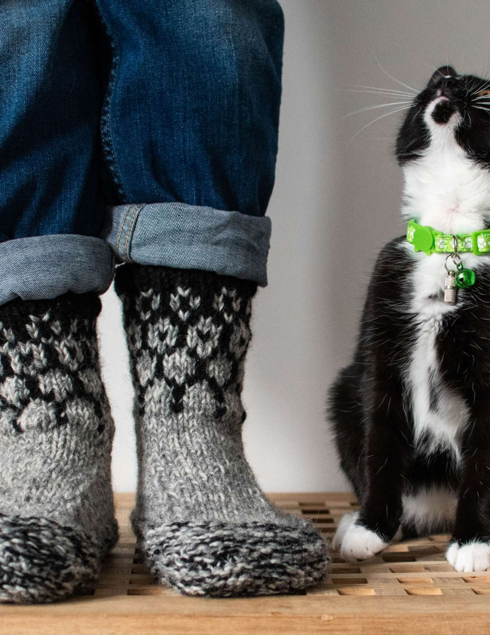a model wears a pair of knitted slippers with colourwork detail on the cuff, they standing on a table with just their feet and cuffs of rolled up jeans showing. Next to them sits a black and white cat with green colour that looks up at the wearer.