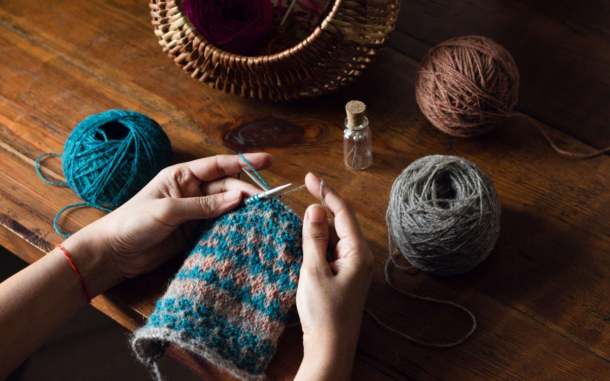 Hands knitting on a colourwork swatch in blue, coral and grey. The knitting is being held over a wooden table and there is a round wicker basket at the top of the photo and a bottle of pins.