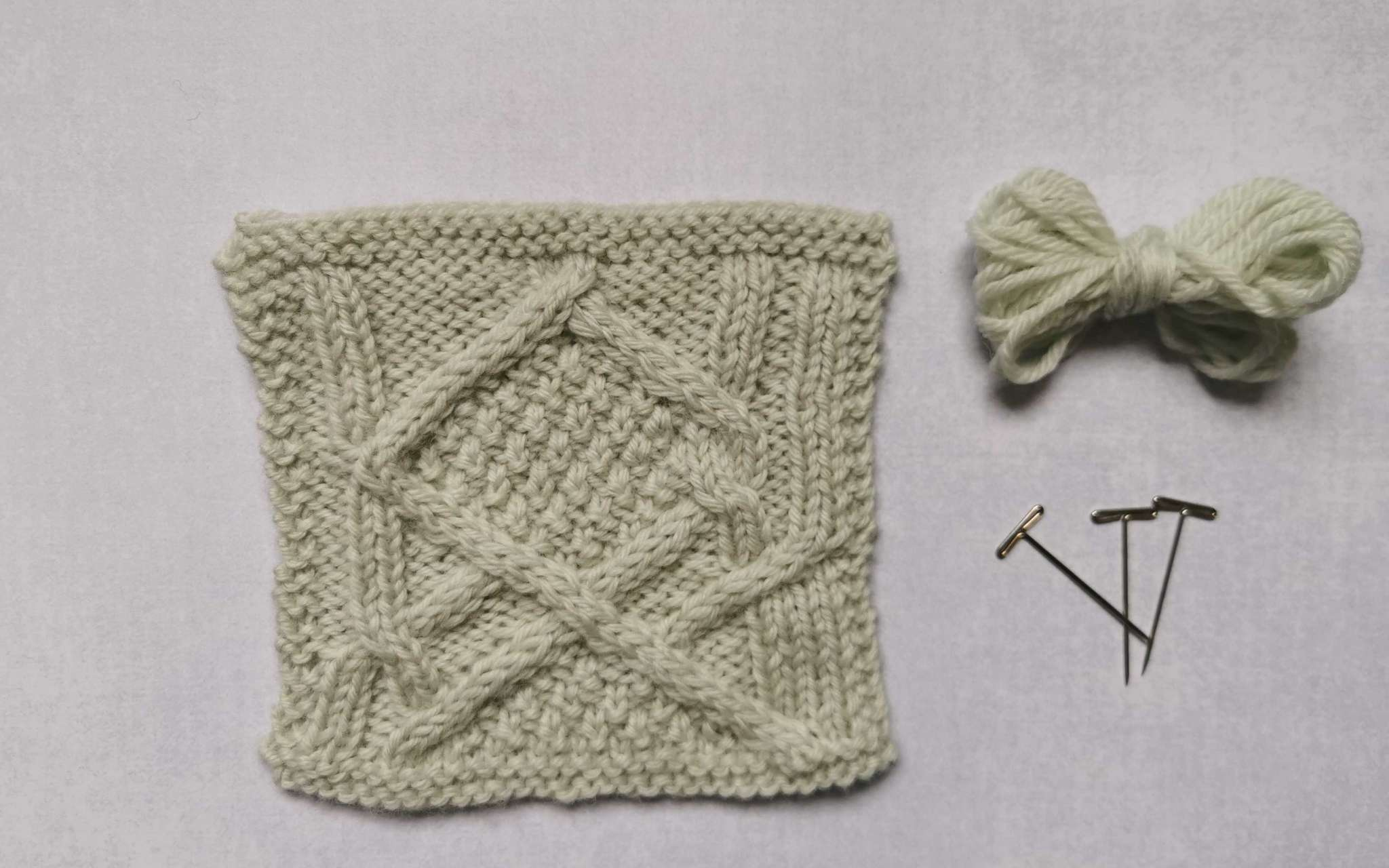 A square swatch of stocking stitch in pale cream, with some bundled up spare yarn and t-pins laying beside it to the right.