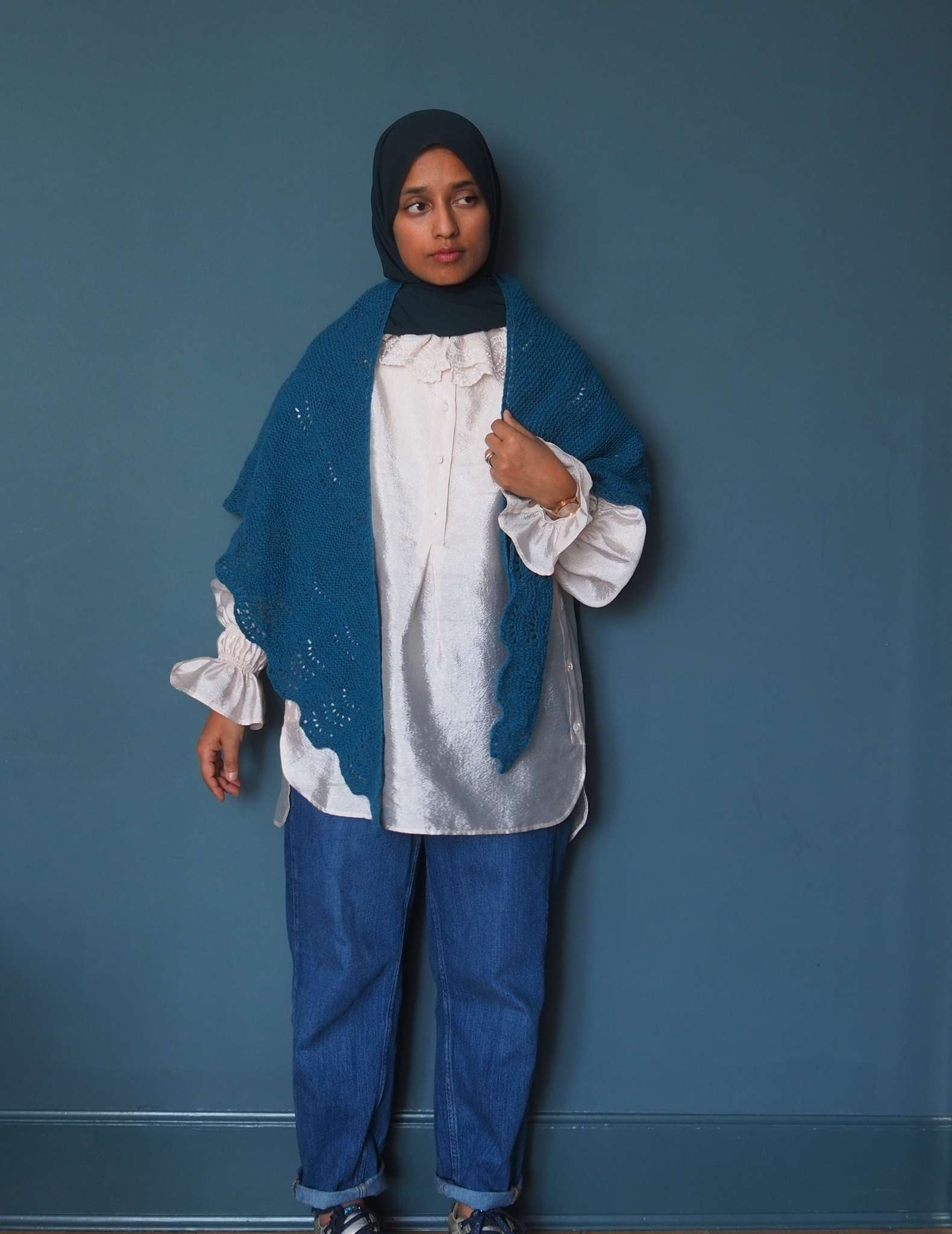 A brown woman in a hijab wears a ruffled white shirt and jeans, and stands in front of a dark blue background. She is wearing a blue wool shawl around her neck with the pointed ends hanging down in the front.
