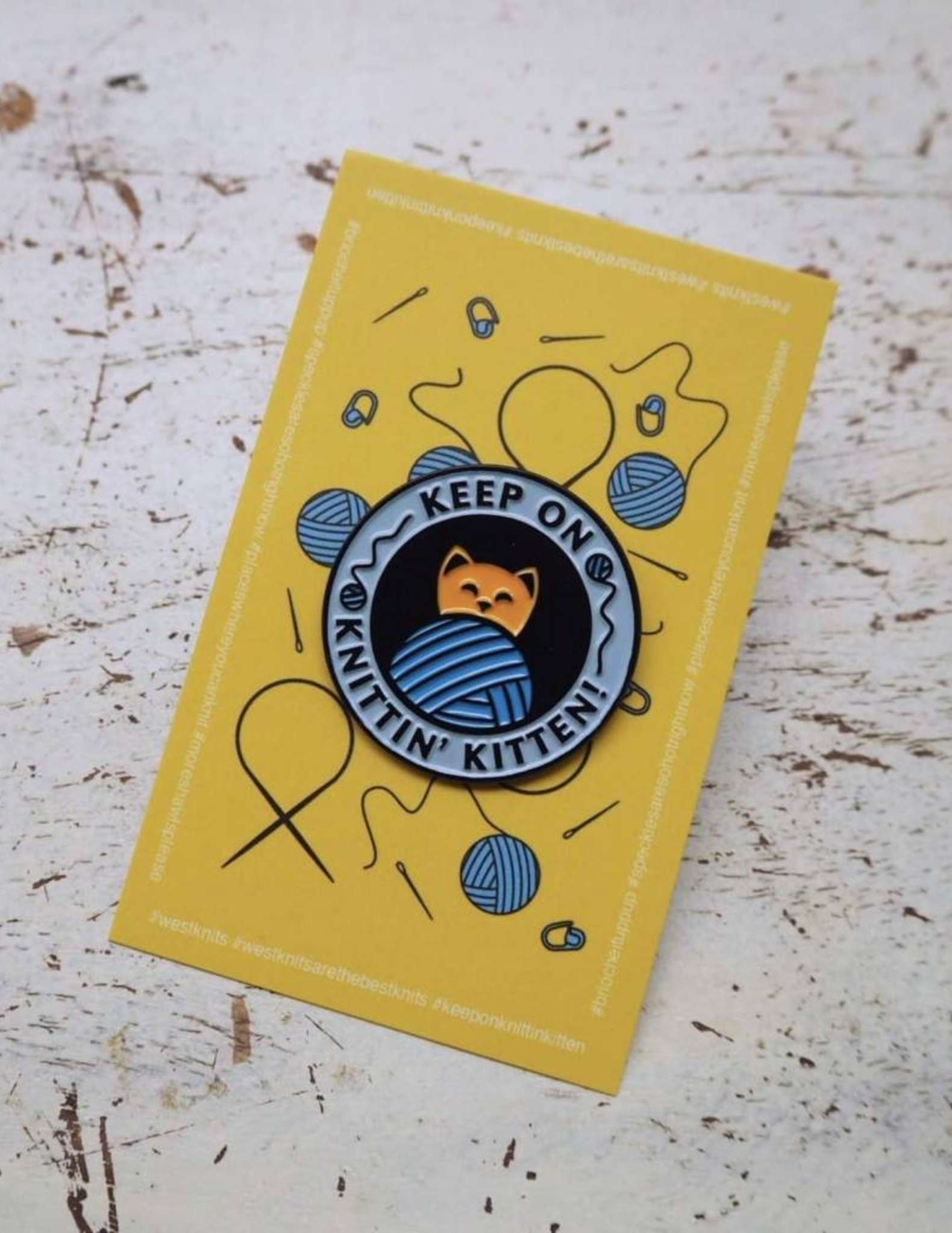 An enamel pin saying 'keep on knittin' kitten' showing a cat and a ball of yarn
