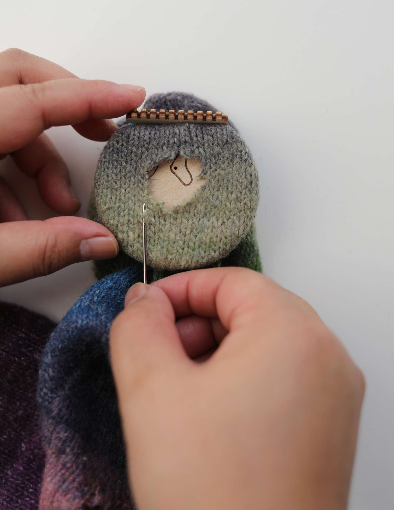 A left hand holds the sock with loom in position, and the right hand holds a needle threaded with black mending thread, with the tip positioned at the bottom left corner of the hole to be mended.