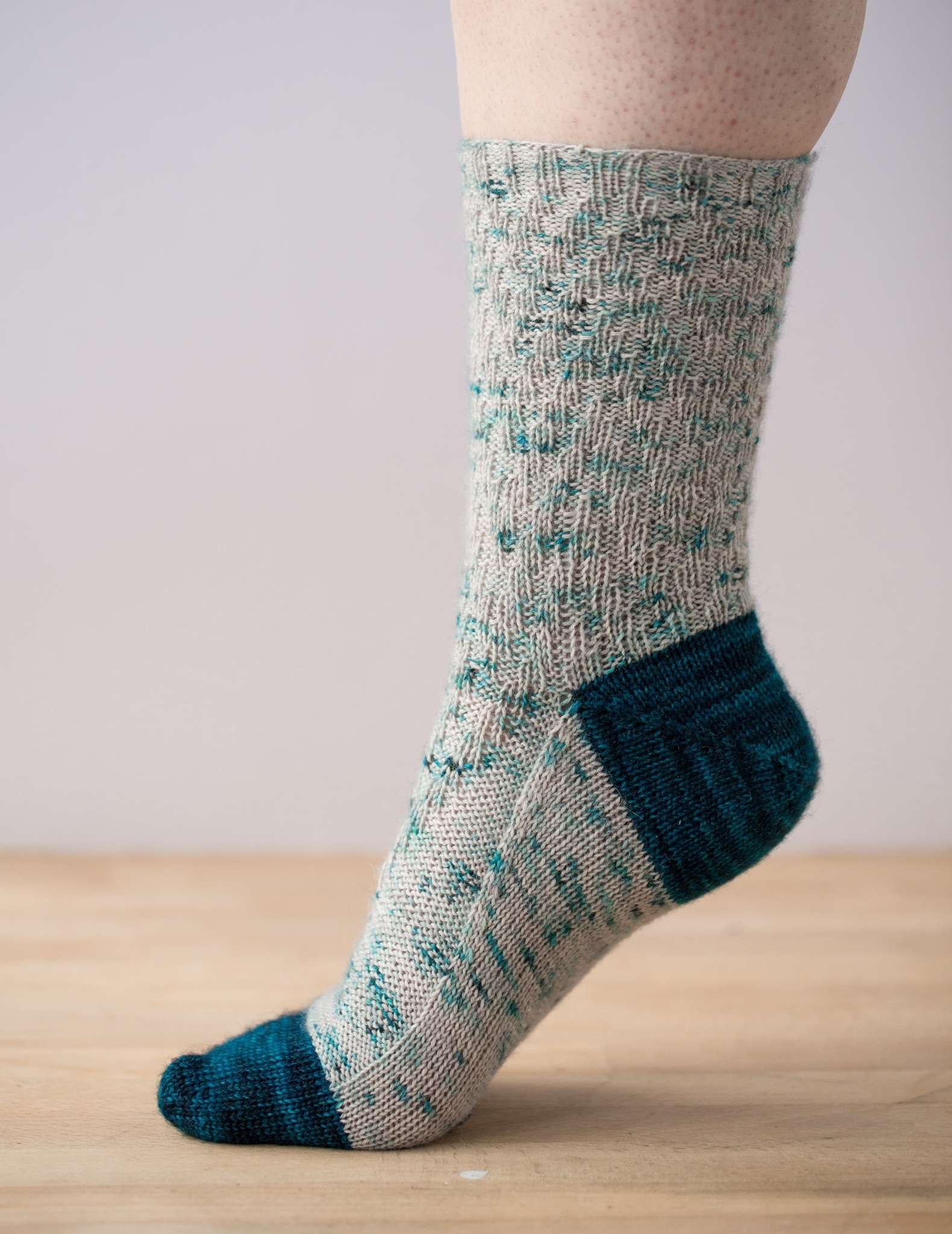 one foot is photographed from the side, with the toe on a wooden surface and the heel raised. The sock has a dark teal toe and heel and a paler textured pattern on the rest of the sock.