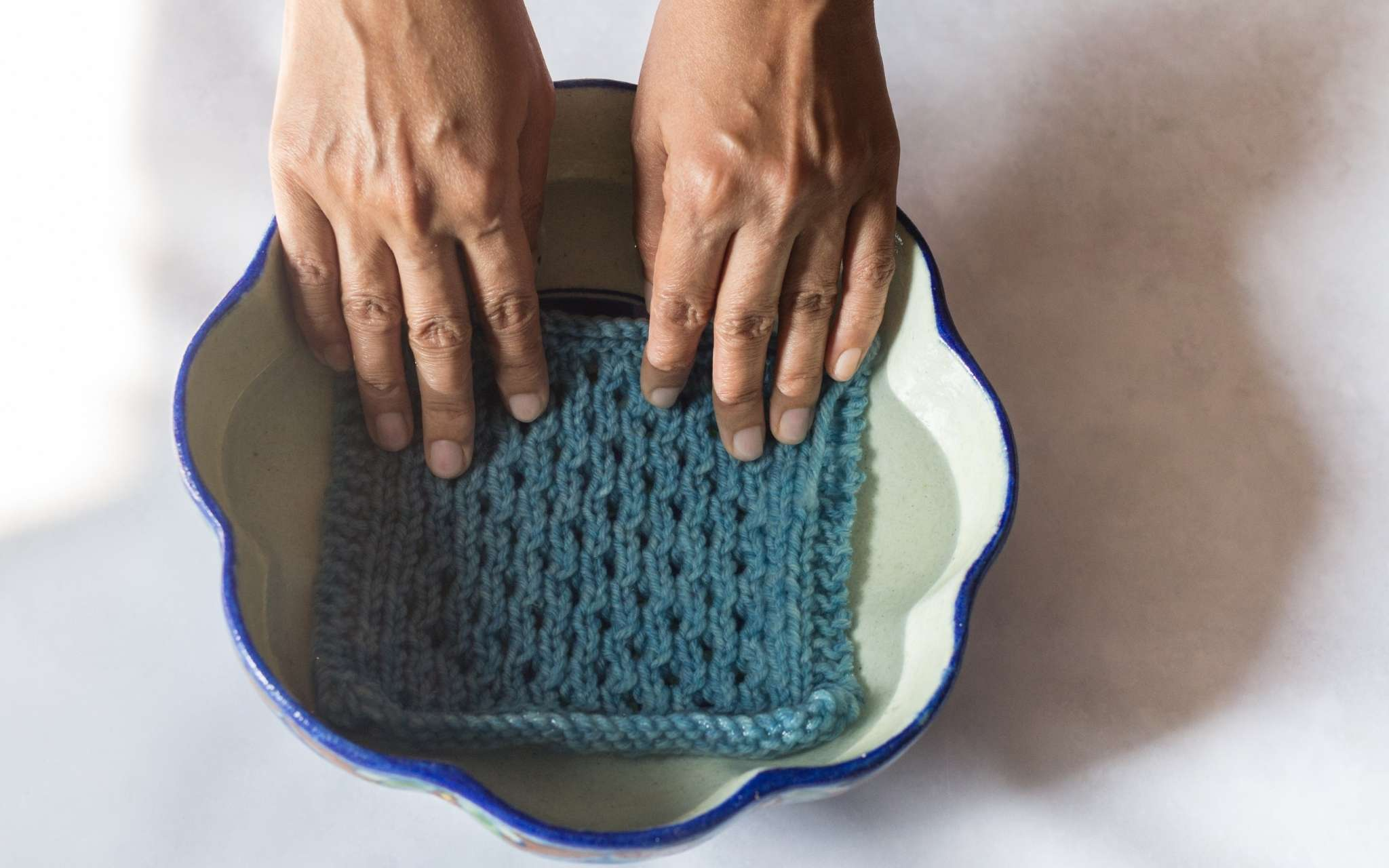 A swatch is being held during water in a small bowl with scalloped shaped edges.